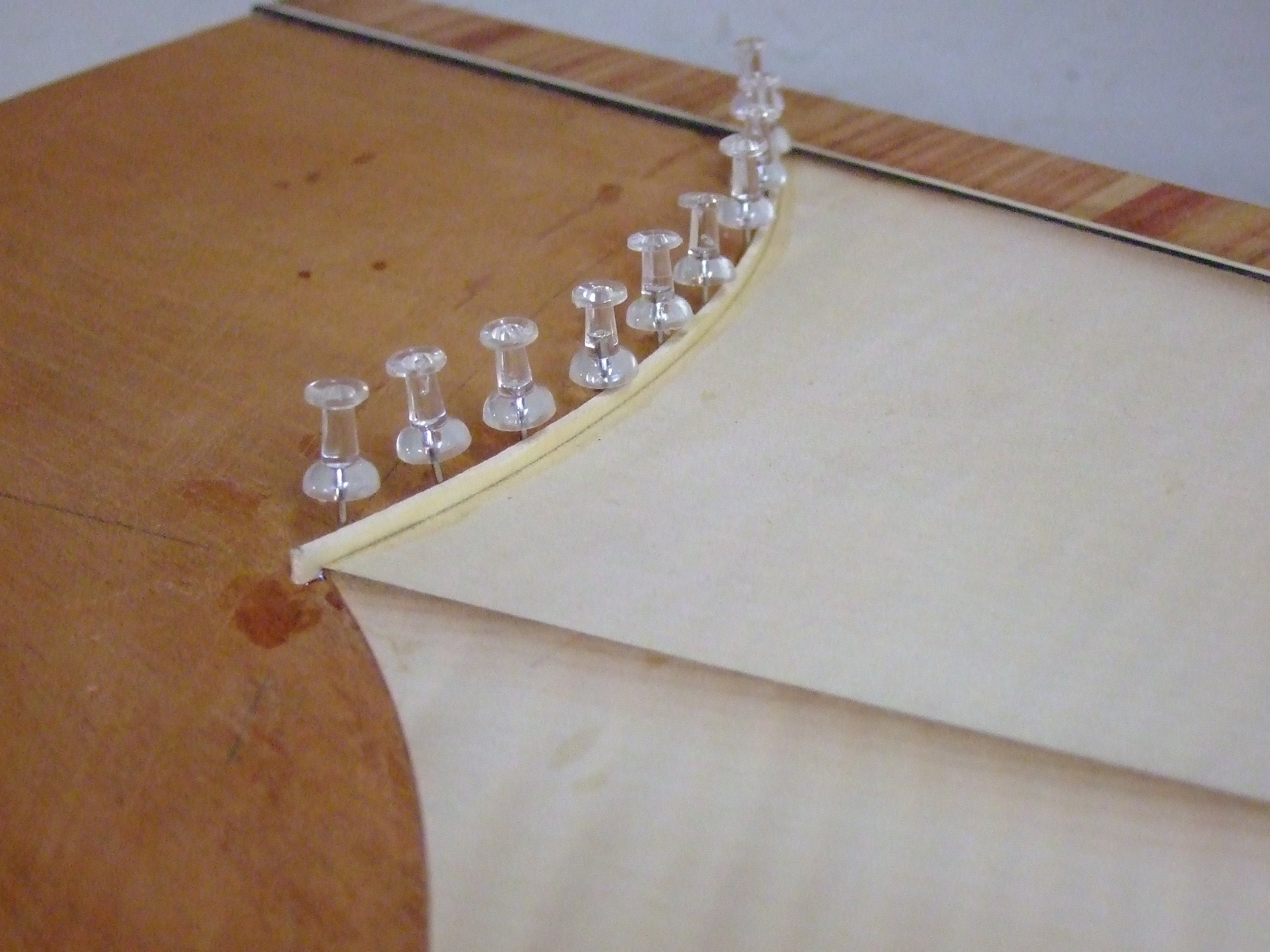 Glueing and clamping holly strings to the edge of the sycamore fan. I made all the strings from solid holly boards because the original strings were thicker than modern veneer.