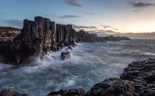 First rays of light hit the rock as the waves crash in.