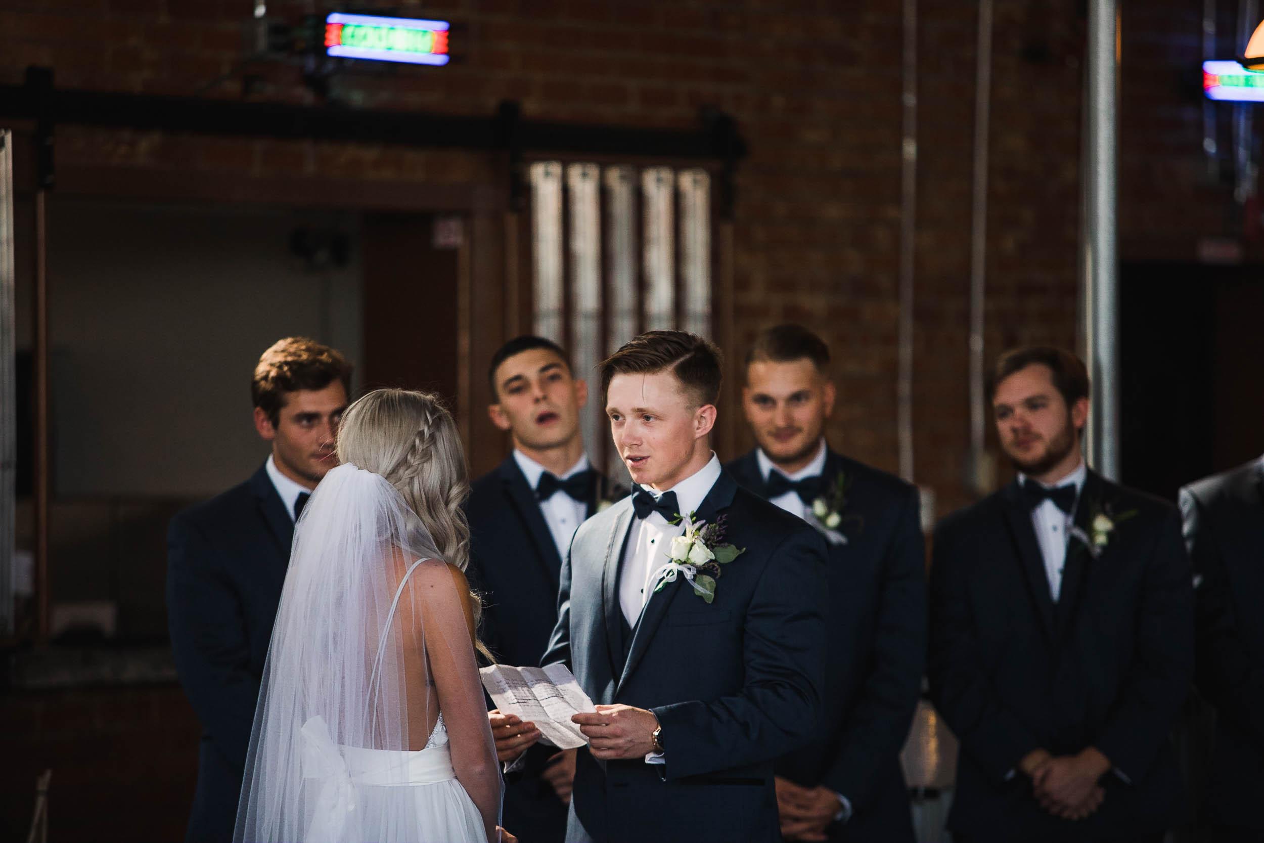 Groom reading wedding vows to his bride