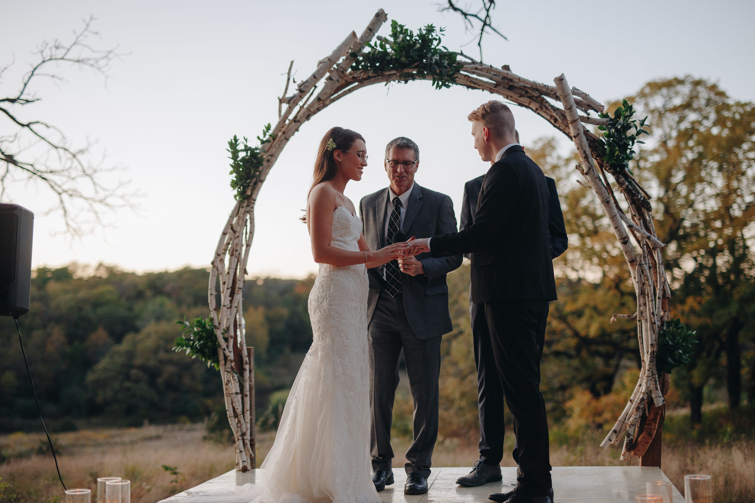 Bride putting ring on groom during wedding ceremony