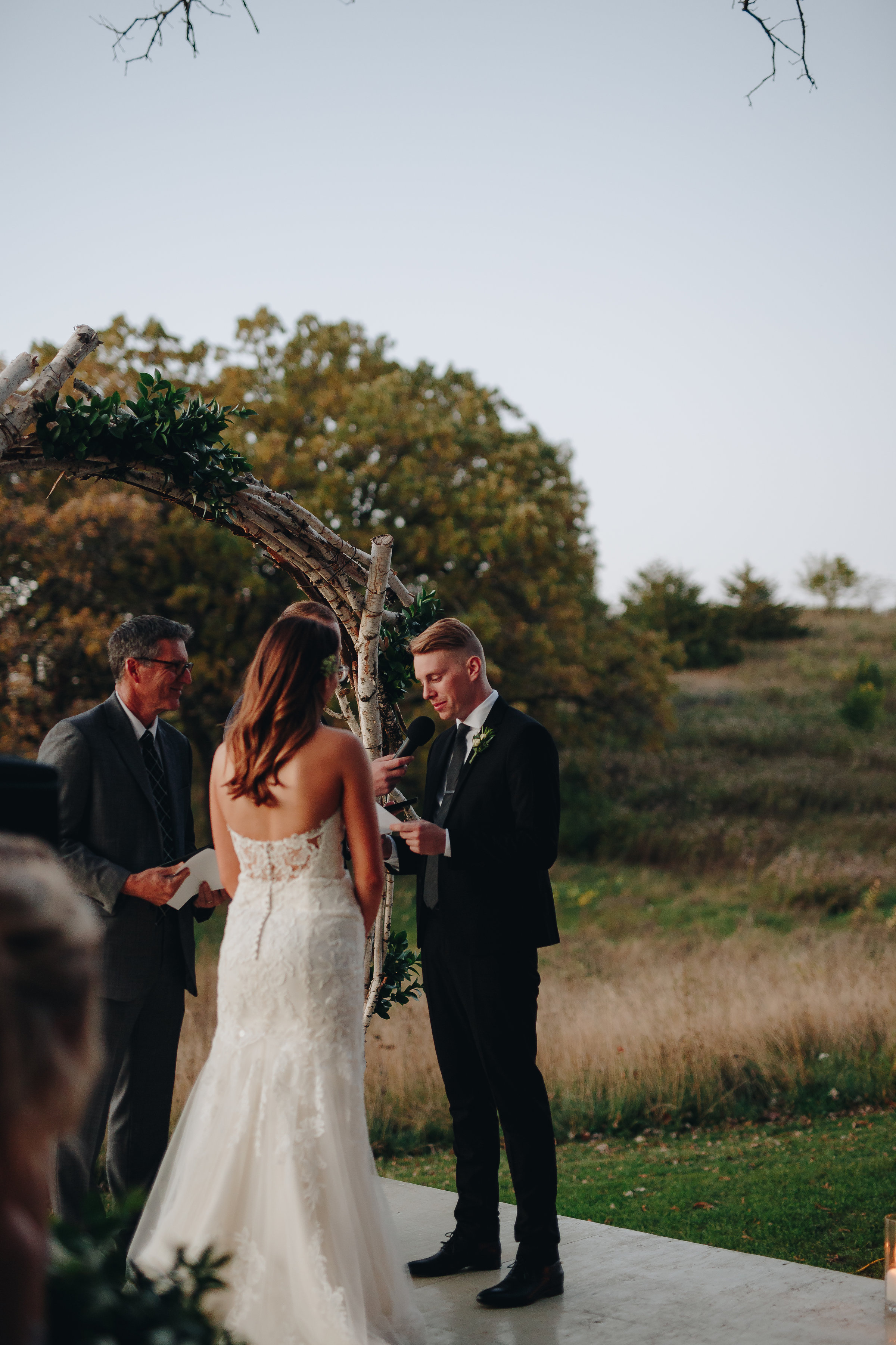 Groom reading vows to his bride at dusk wedding ceremony in Minnesota