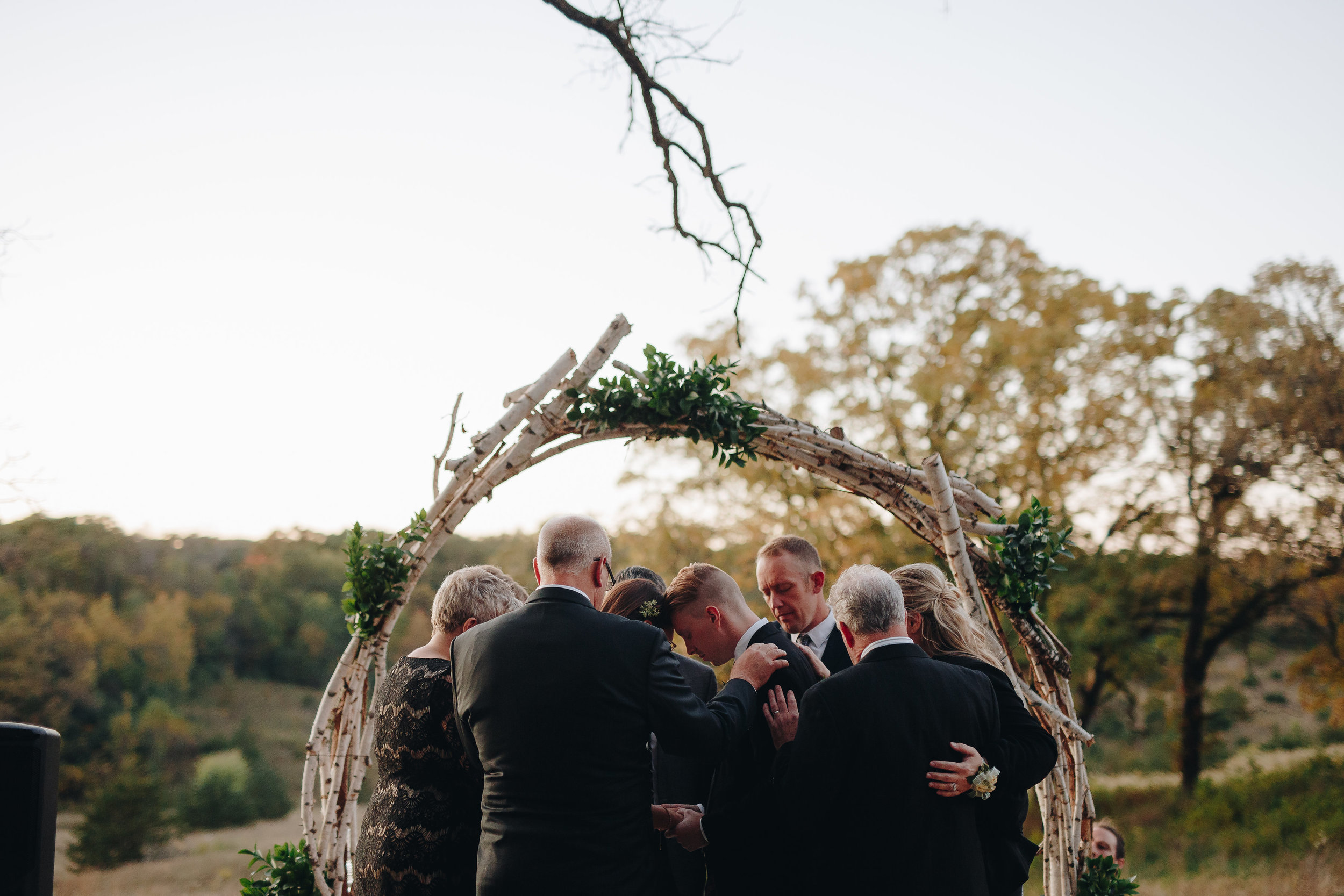 Family lay hands on and prays over bride and groom at Minnesota wedding ceremony