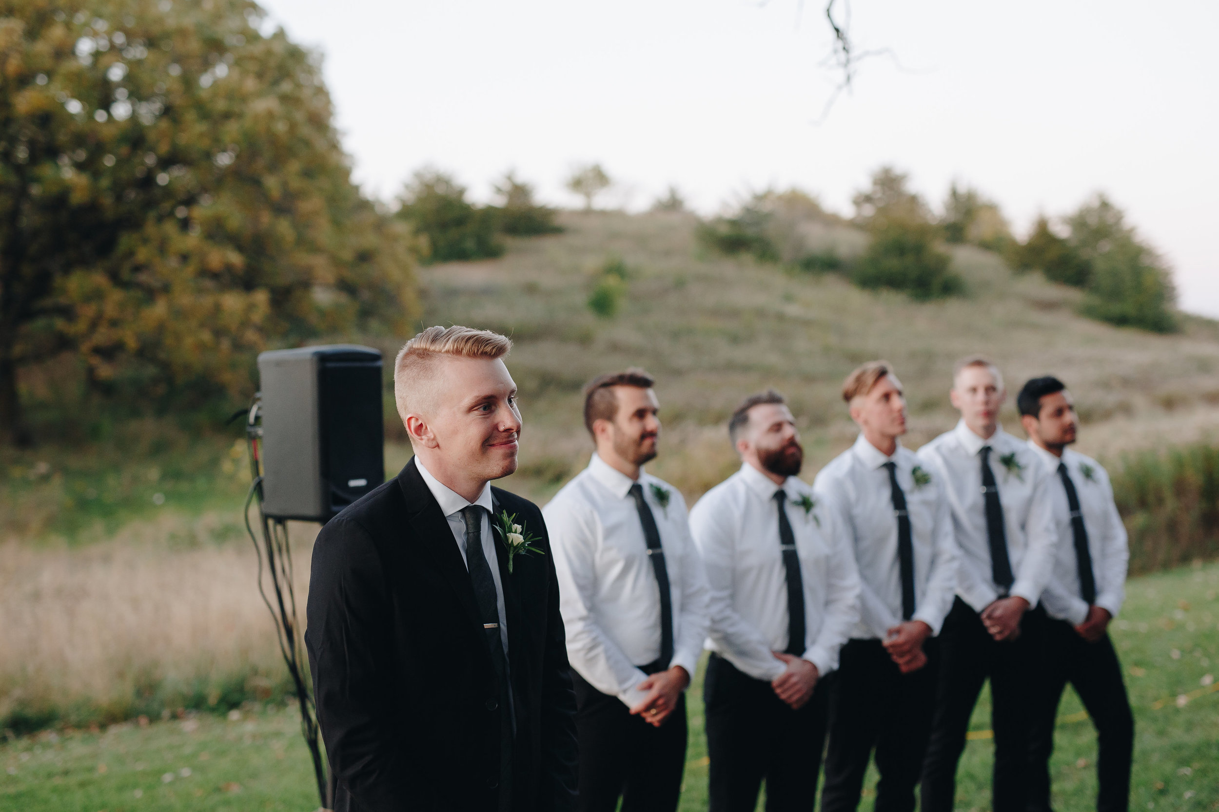 Groom and his groomsmen watch bride walk down the aisle