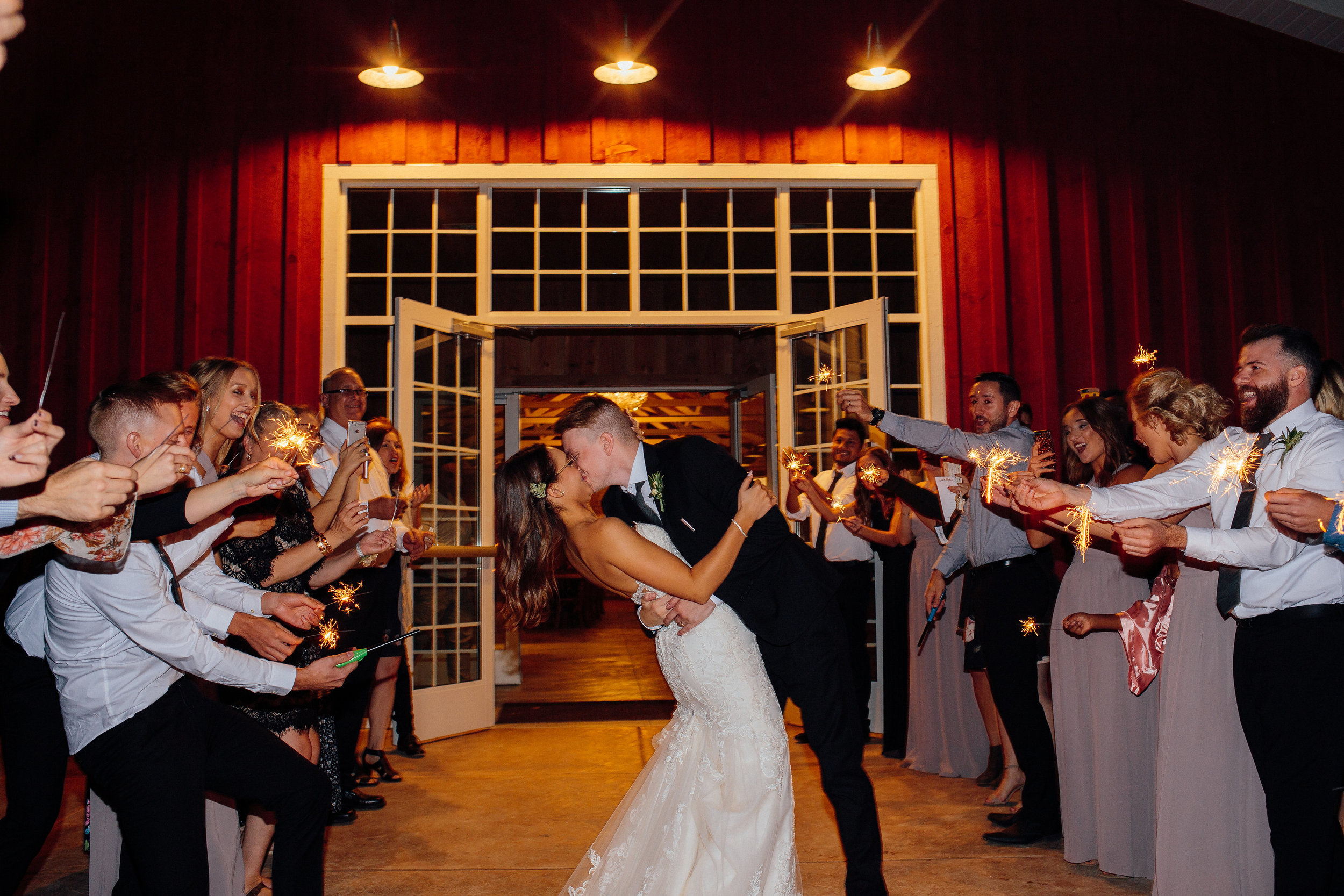 Epic wedding exit bride and groom kiss surrounded by guests in Minnesota wedding