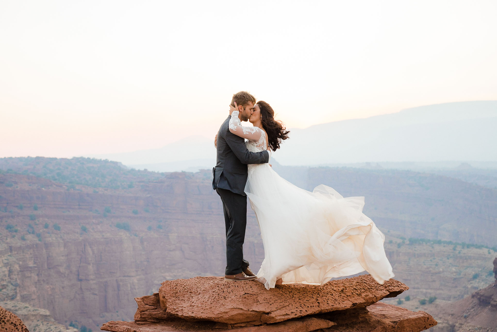 Couple kisses on a canyon edge in Capitol Reef National Park, Utah