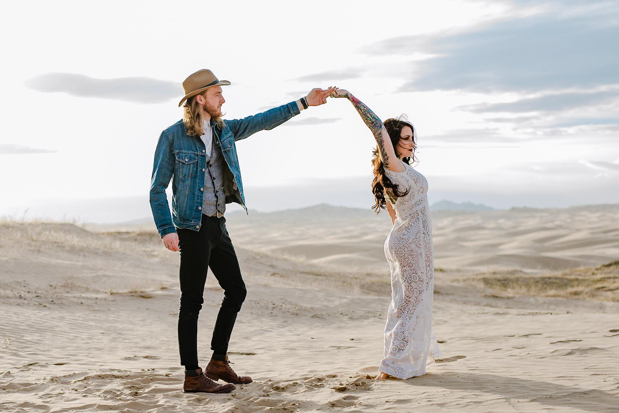 Couple in alternative wedding clothes dance at the Little Sahara Sand Dunes, Utah