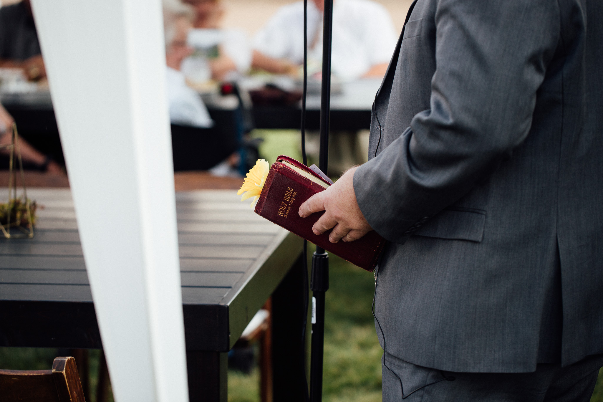 Groom's dad holds Bible during speech at wedding dinner