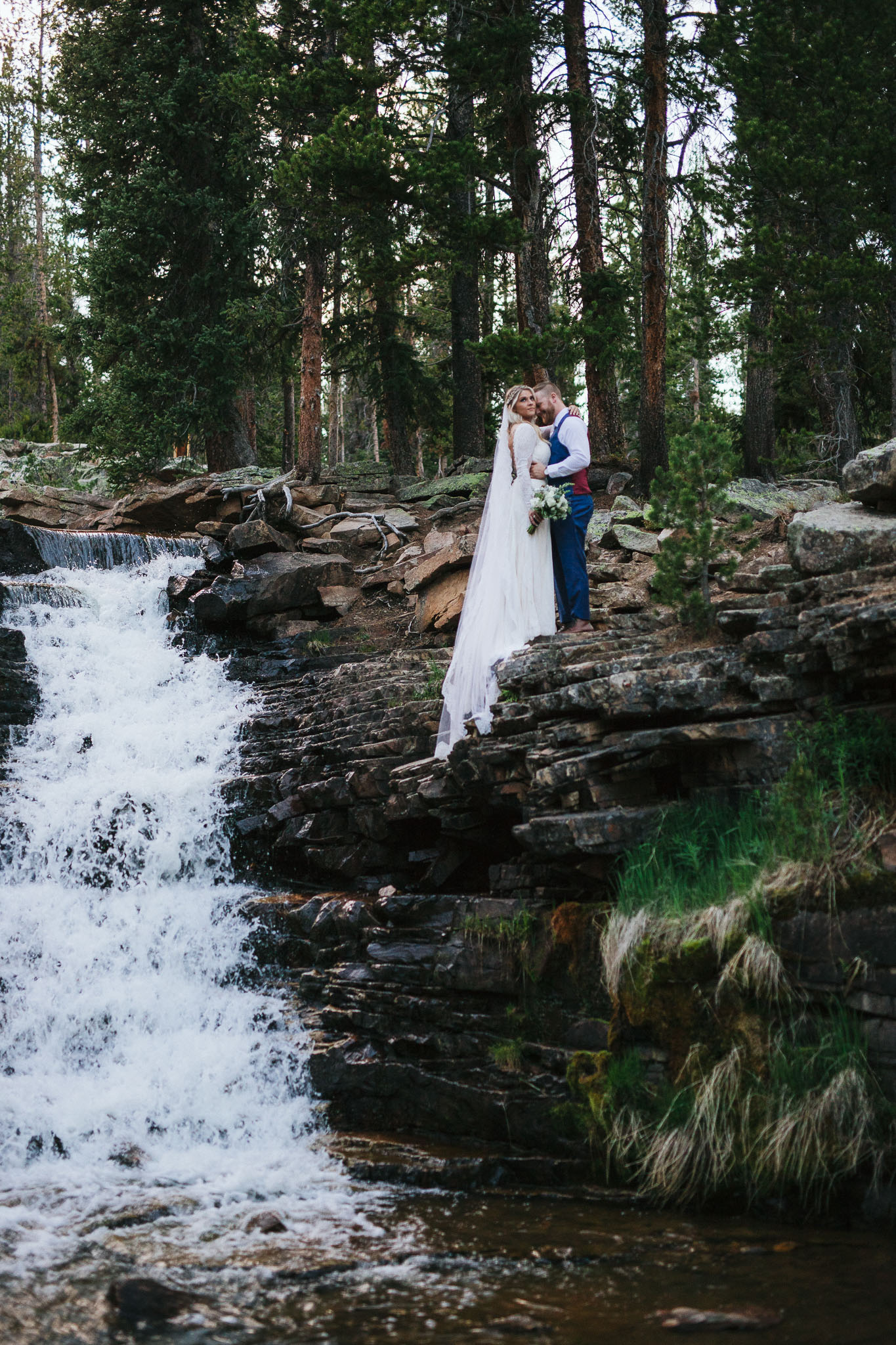 Bride and Groom pose for wedding photos at Provo Falls in the Utah Mountains