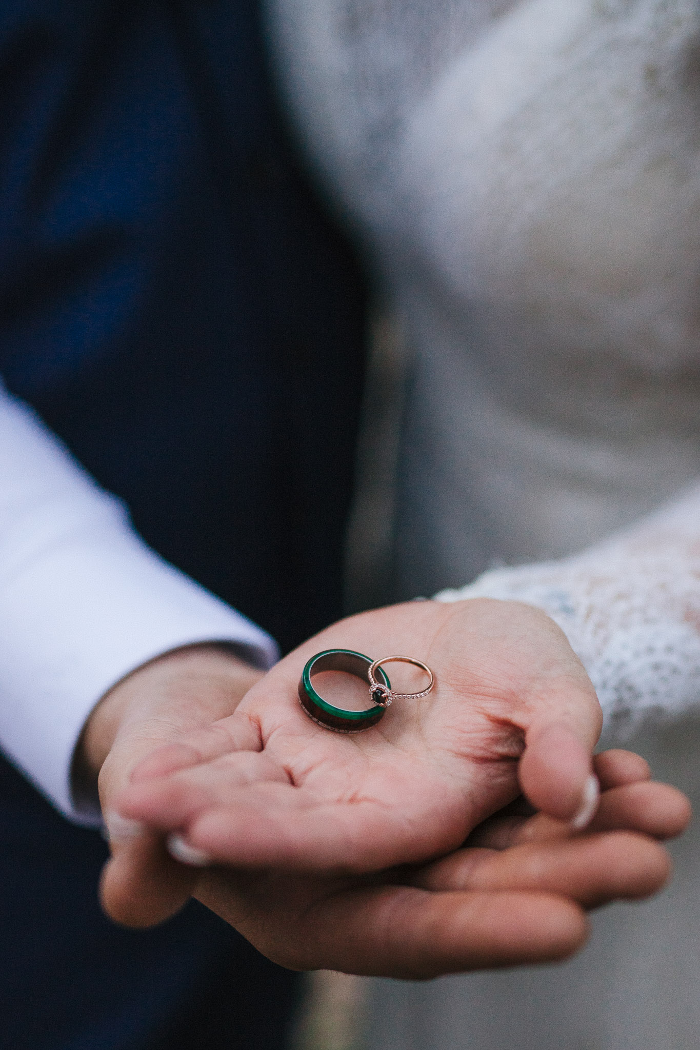 Bride and groom hold wedding rings