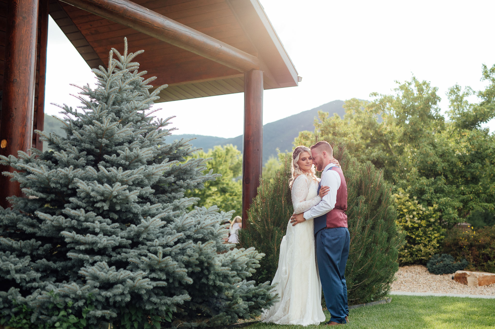Bride and Groom pose for photos during wedding at cabin in Utah Mountains