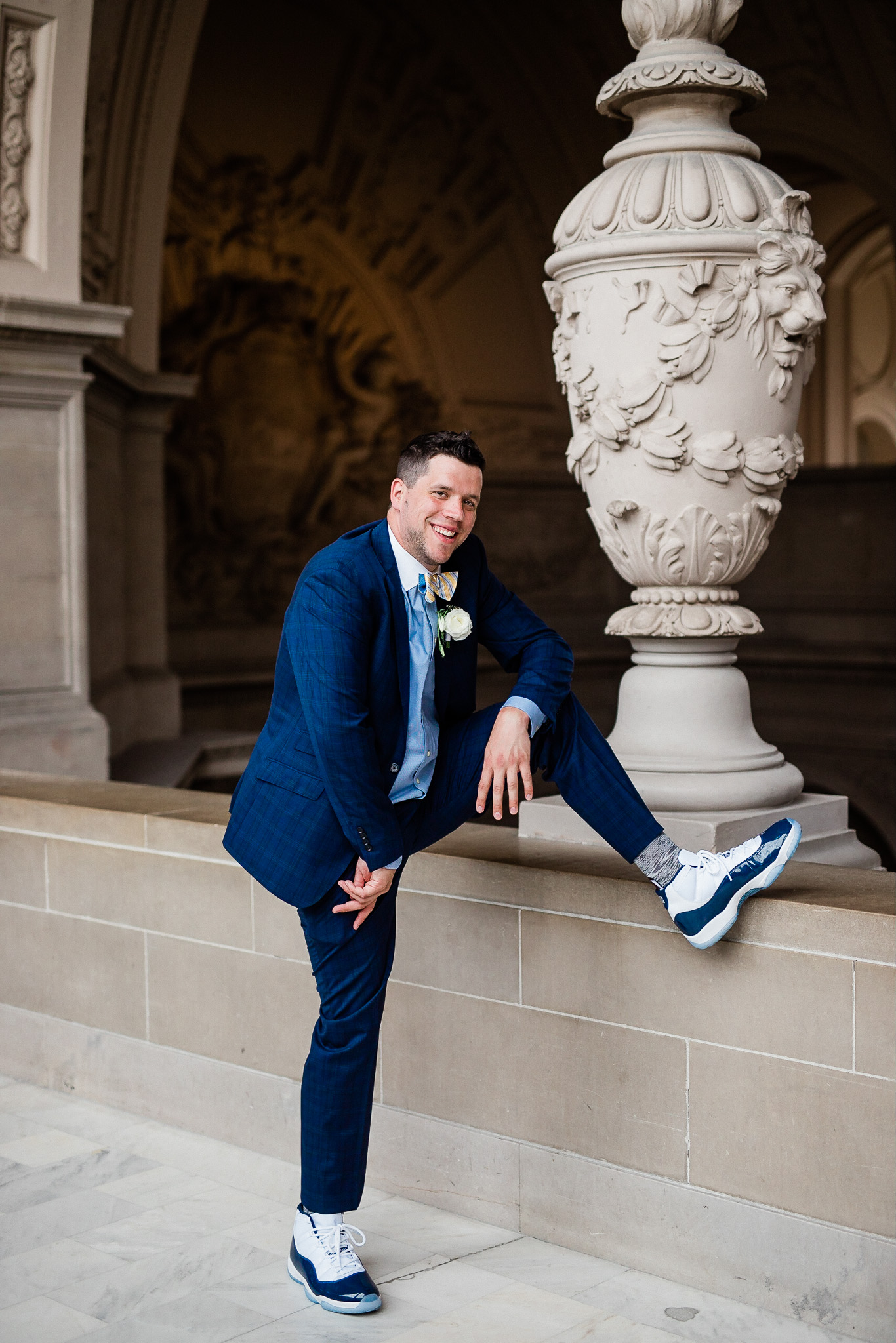 Groom poses for wedding portraits in San Francisco City Hall