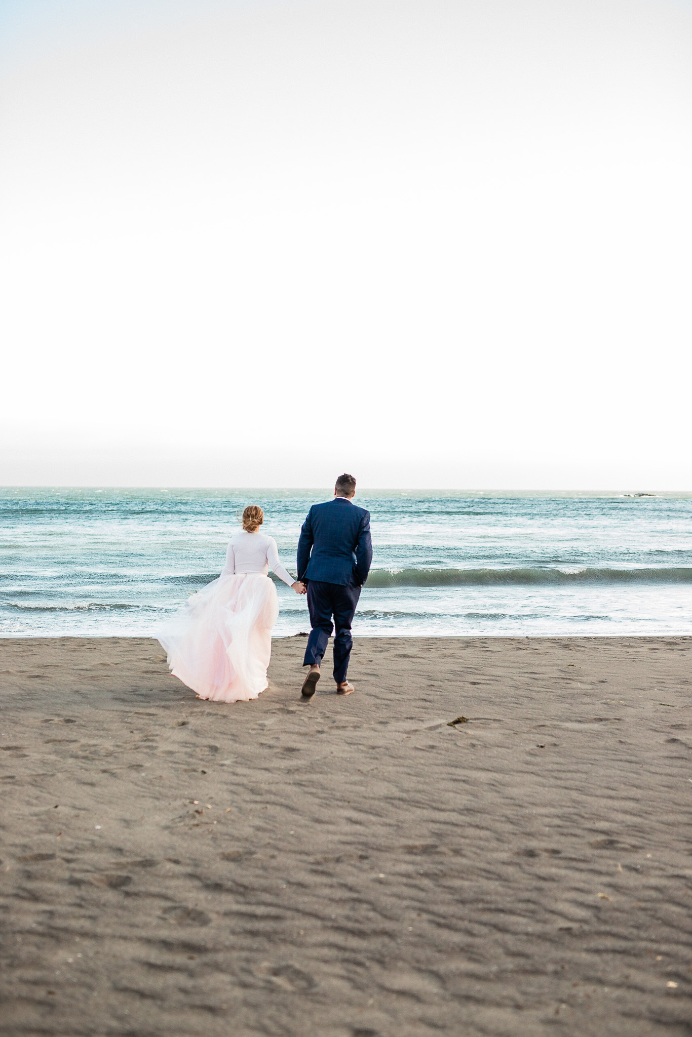 Bride and Groom pose for wedding photos on the beach near San Francisco