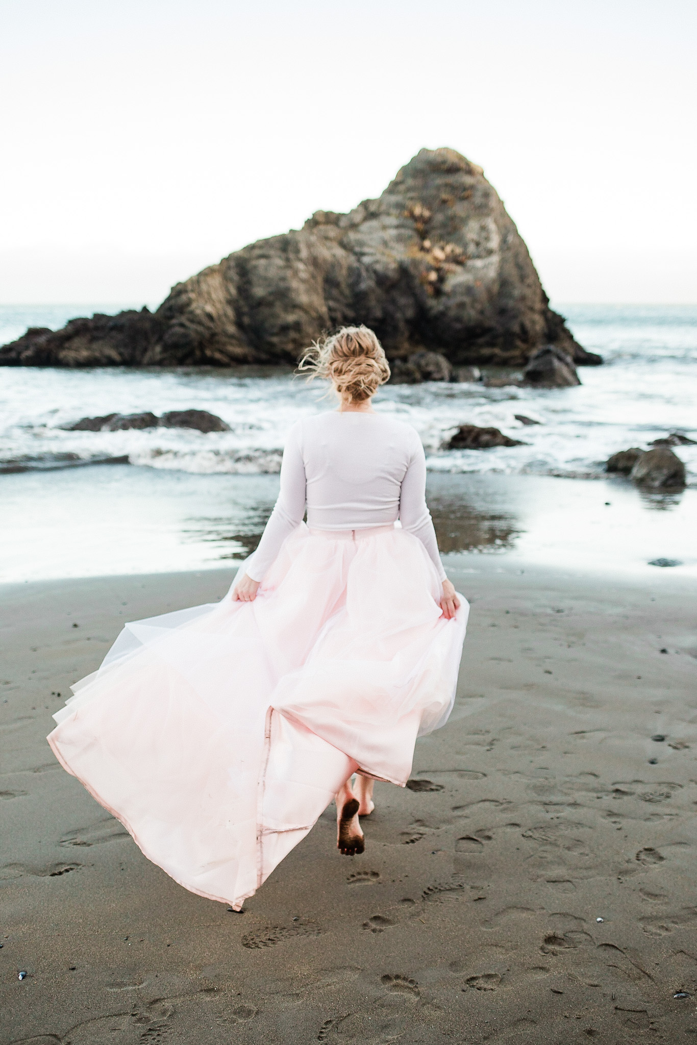 Bride poses for wedding photos on the beach near San Francisco