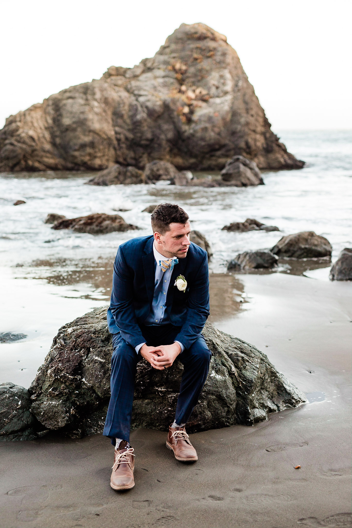 Groom pose for wedding photos on the beach near San Francisco