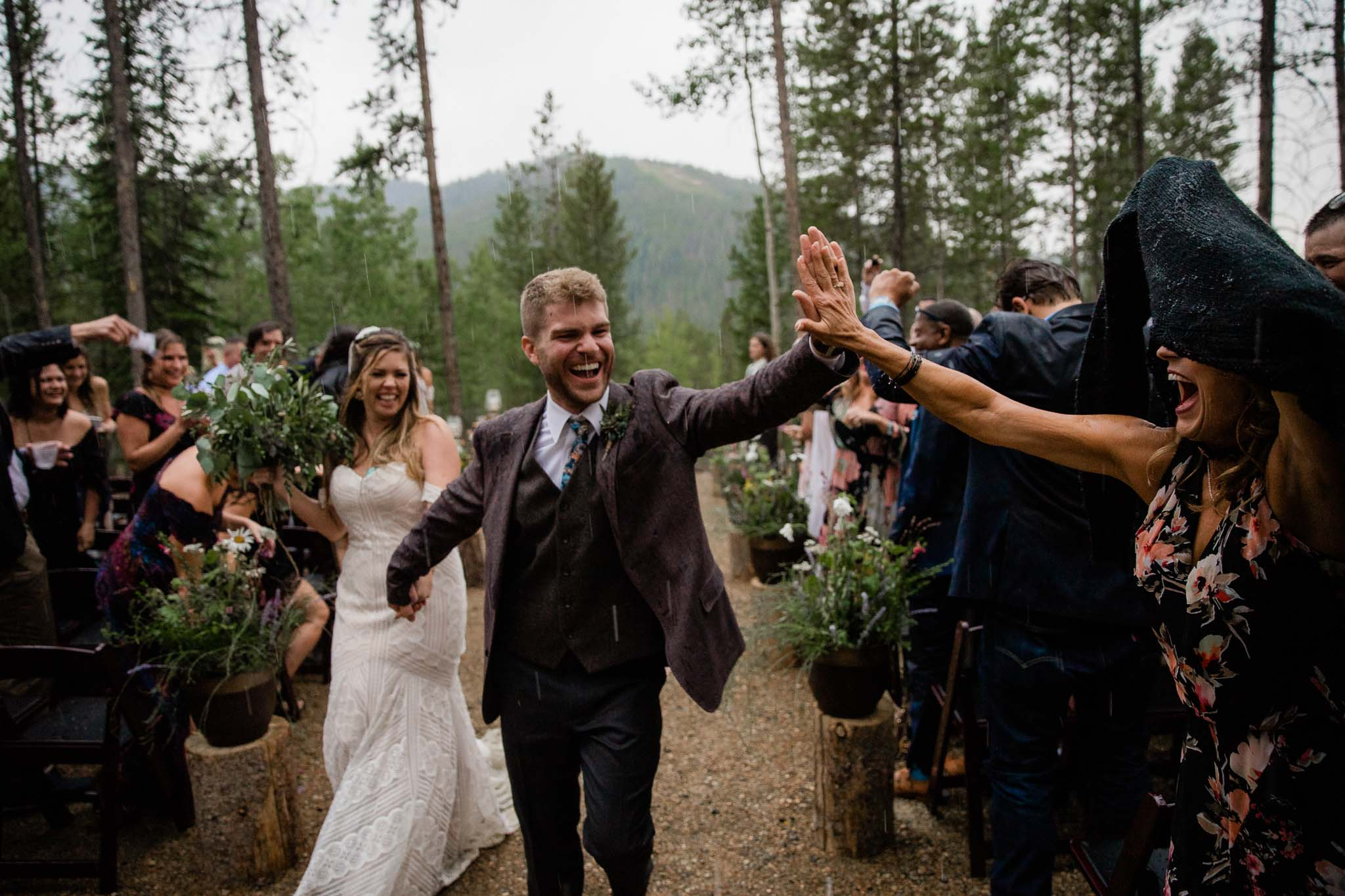 Groom high fives guest during recessional after rainy wedding ceremony in Winter Park, Colorado