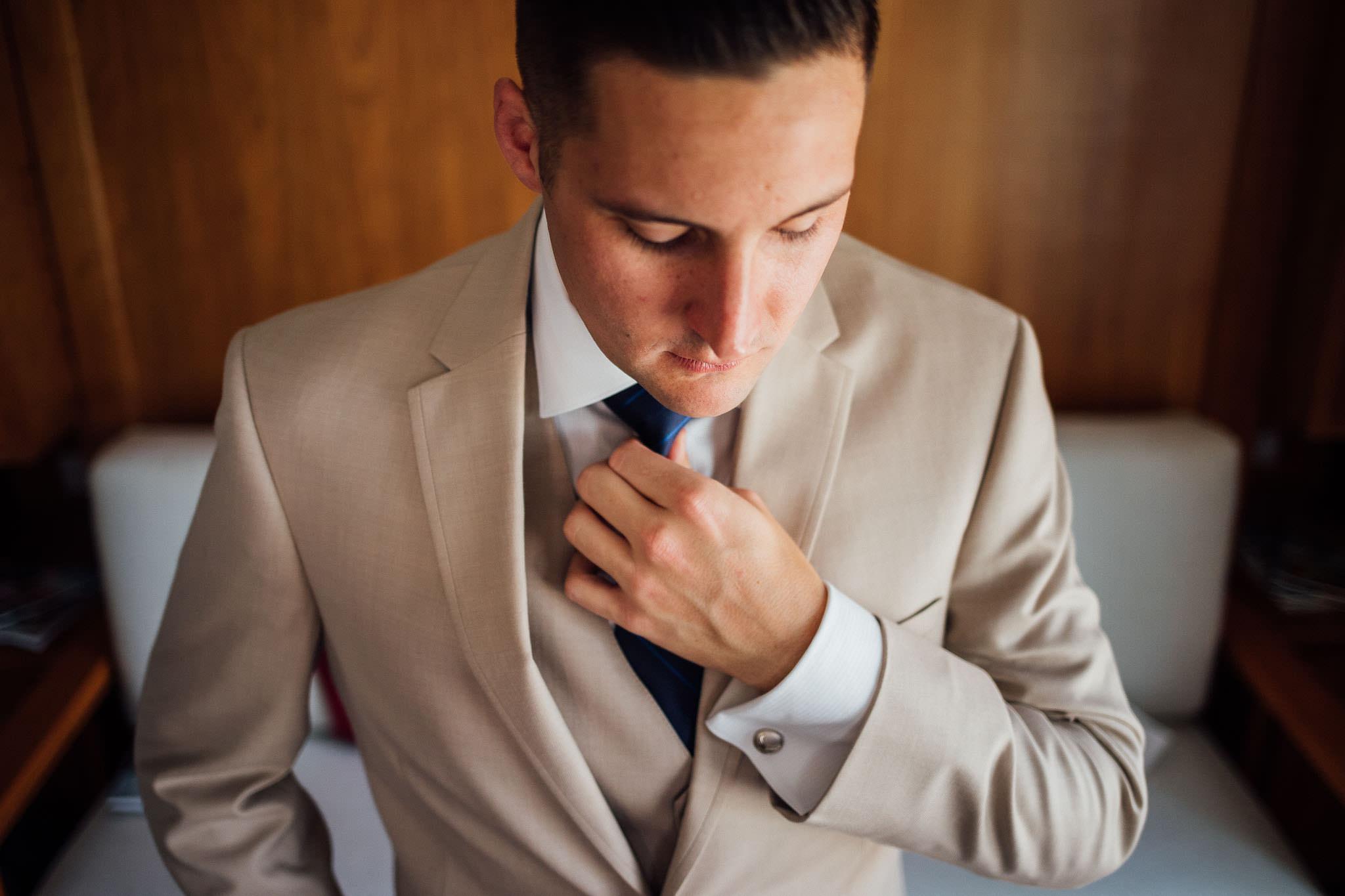 Close up portrait of groom in tux adjusting tie in Waco, Texas