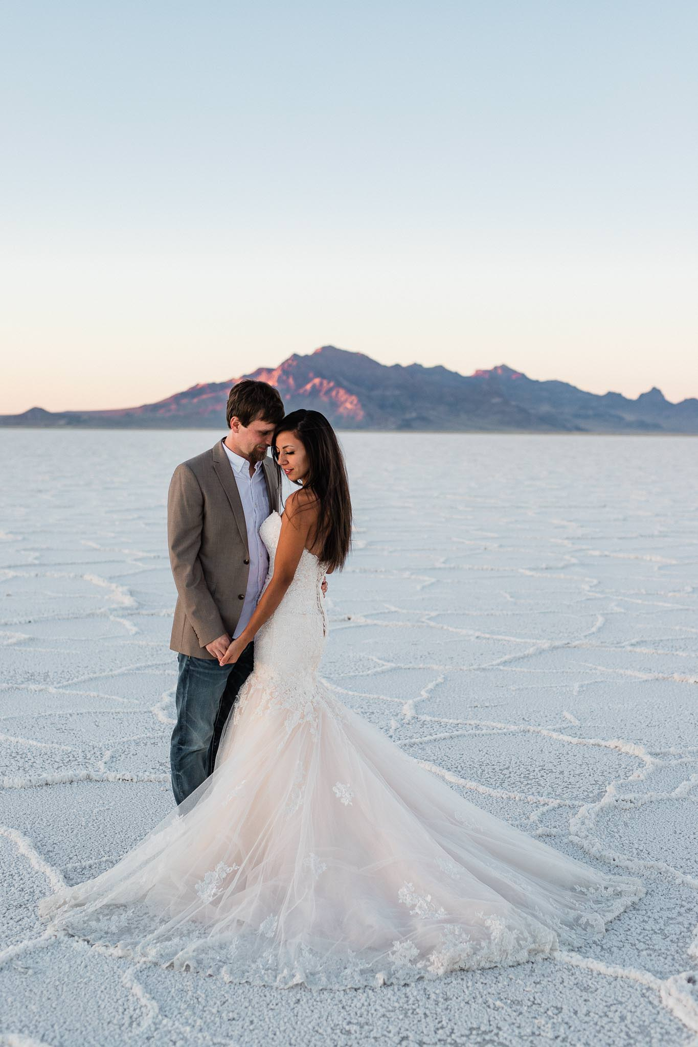 Intimate wedding couple portrait on Bonneville Salt Flats in Utah with alpenglow on mountains in the background