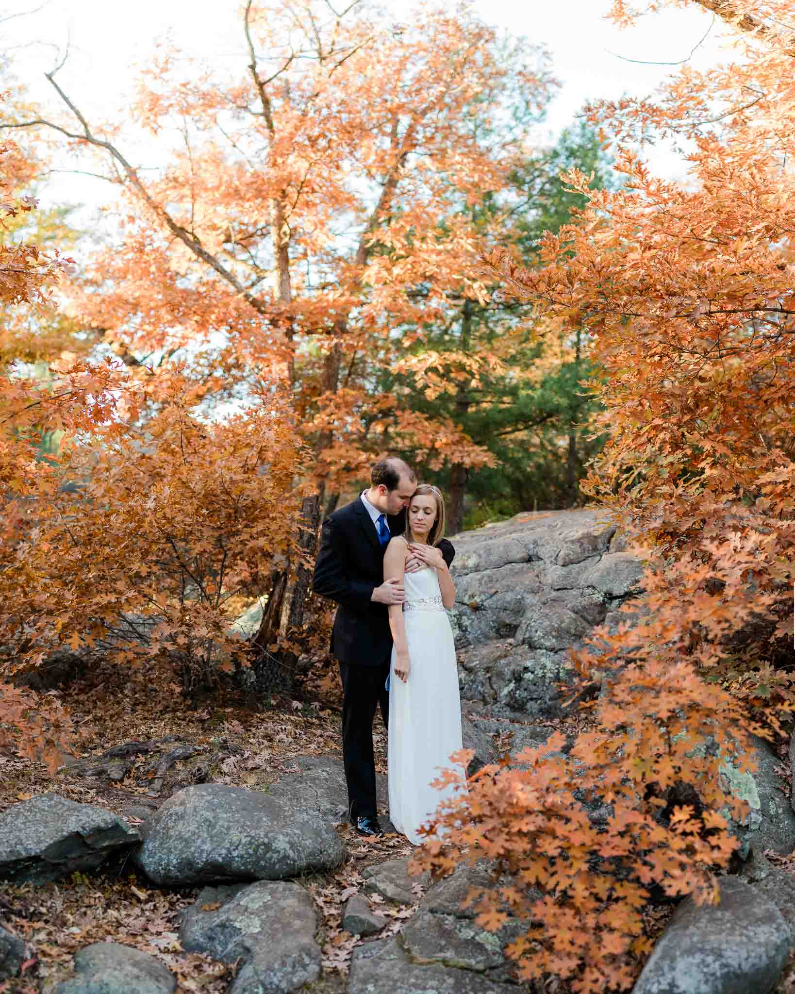 Bride and groom snuggle for intimate portrait surrounded by fall colors near Minneapolis Minnesota