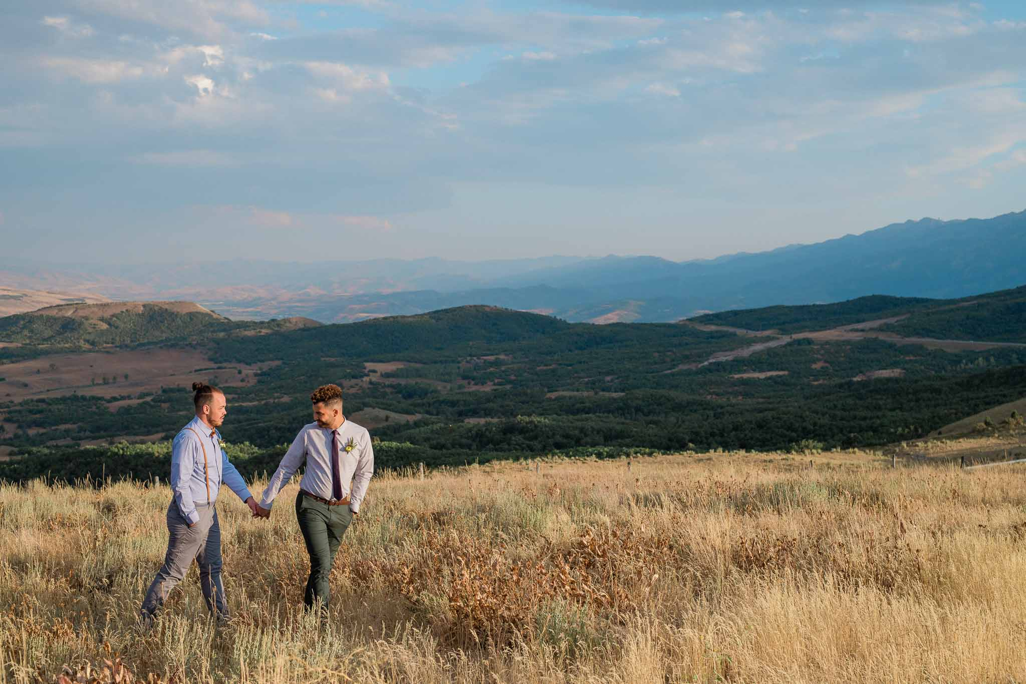 Two grooms walk on field with mountain landscape in the background in Utah