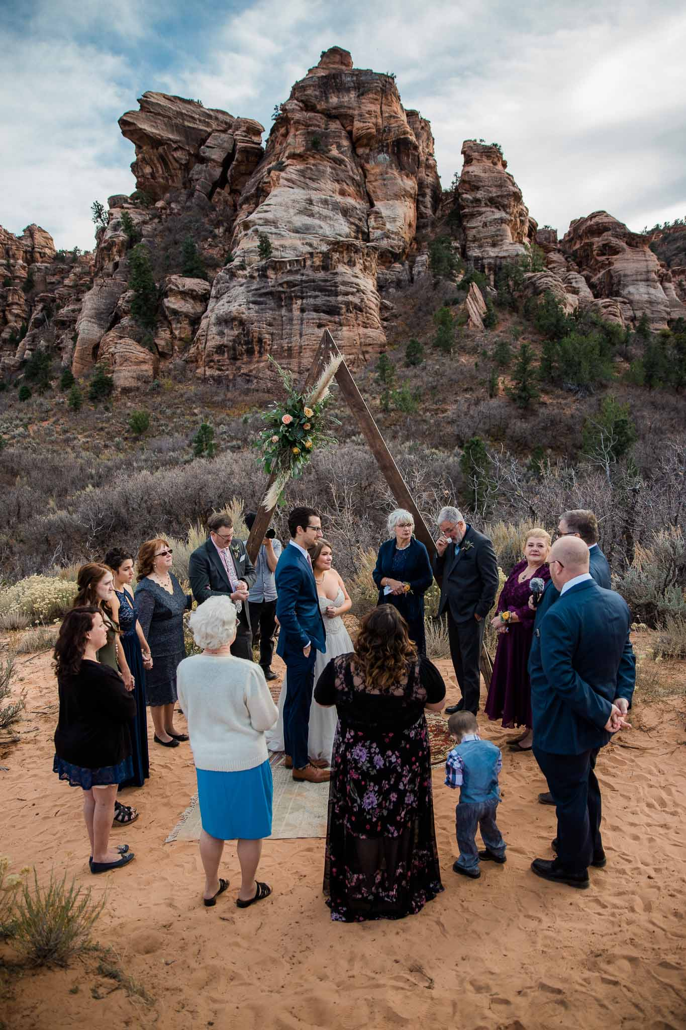 Family gathers around couple for blessing during their intimate wedding ceremony in Zion National Park Utah