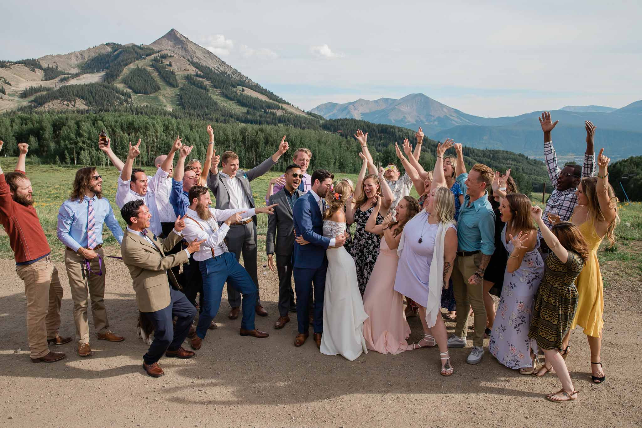 Friends and family cheer while bride and groom kiss in front of Ten Peaks view in Crested Butte Colorado