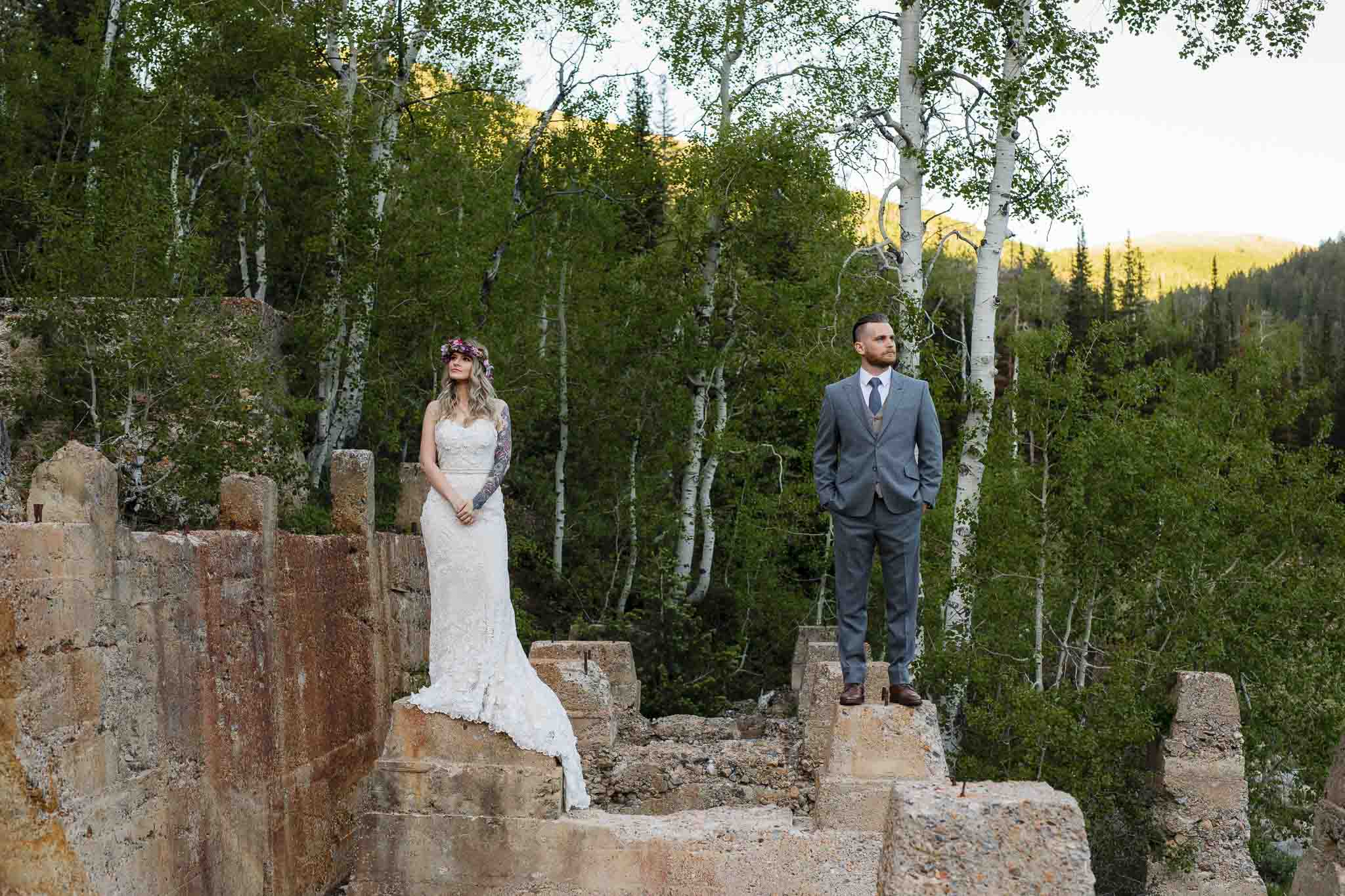 Bride and groom stand apart on ruins in forest for editorial style wedding portrait in the Wasatch Mountains in Utah