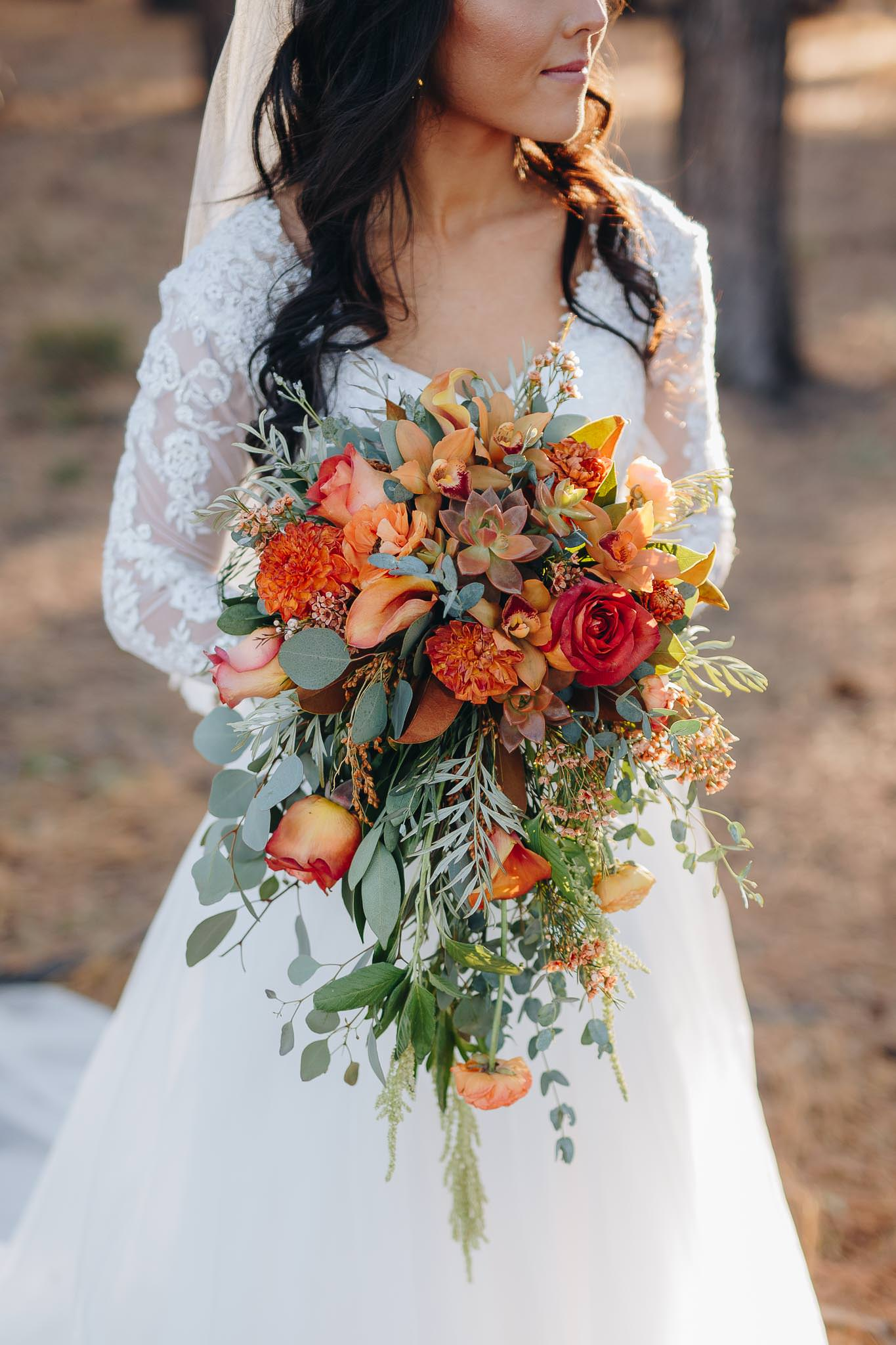 Close up of bride holding fall color themed wedding bouquet at the Grand Canyon