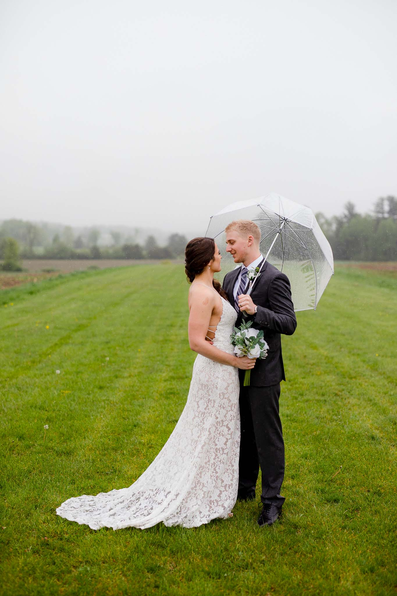 Bride and groom pose under clear umbrella during their rainy wedding day in Lake George, New York
