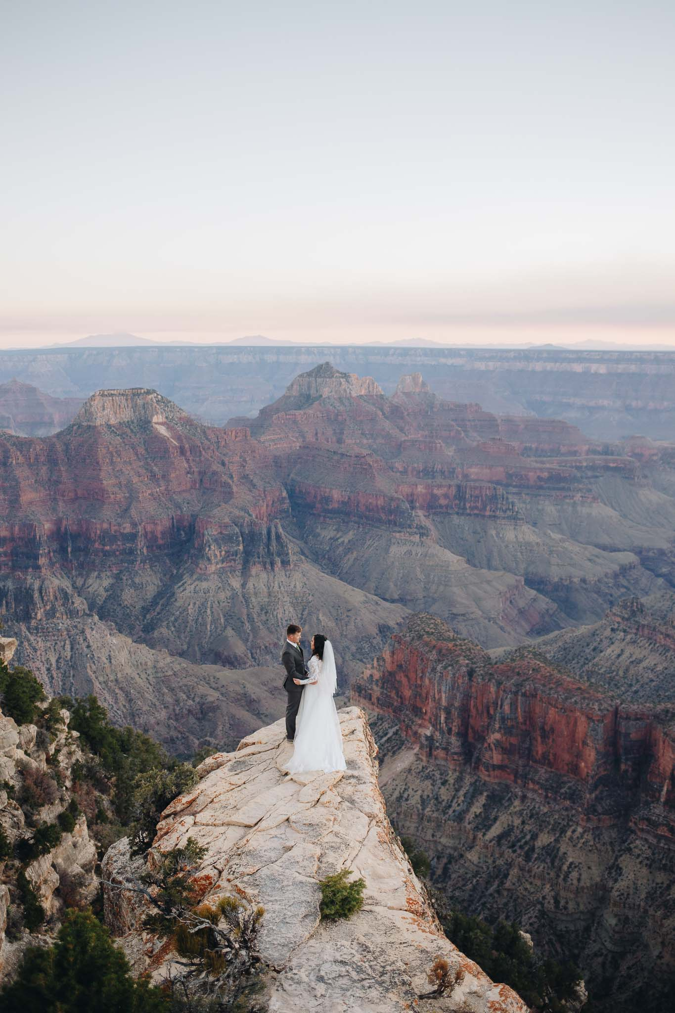 Bride and groom stand together overlook the North Rim of the Grand Canyon for their adventure wedding portraits