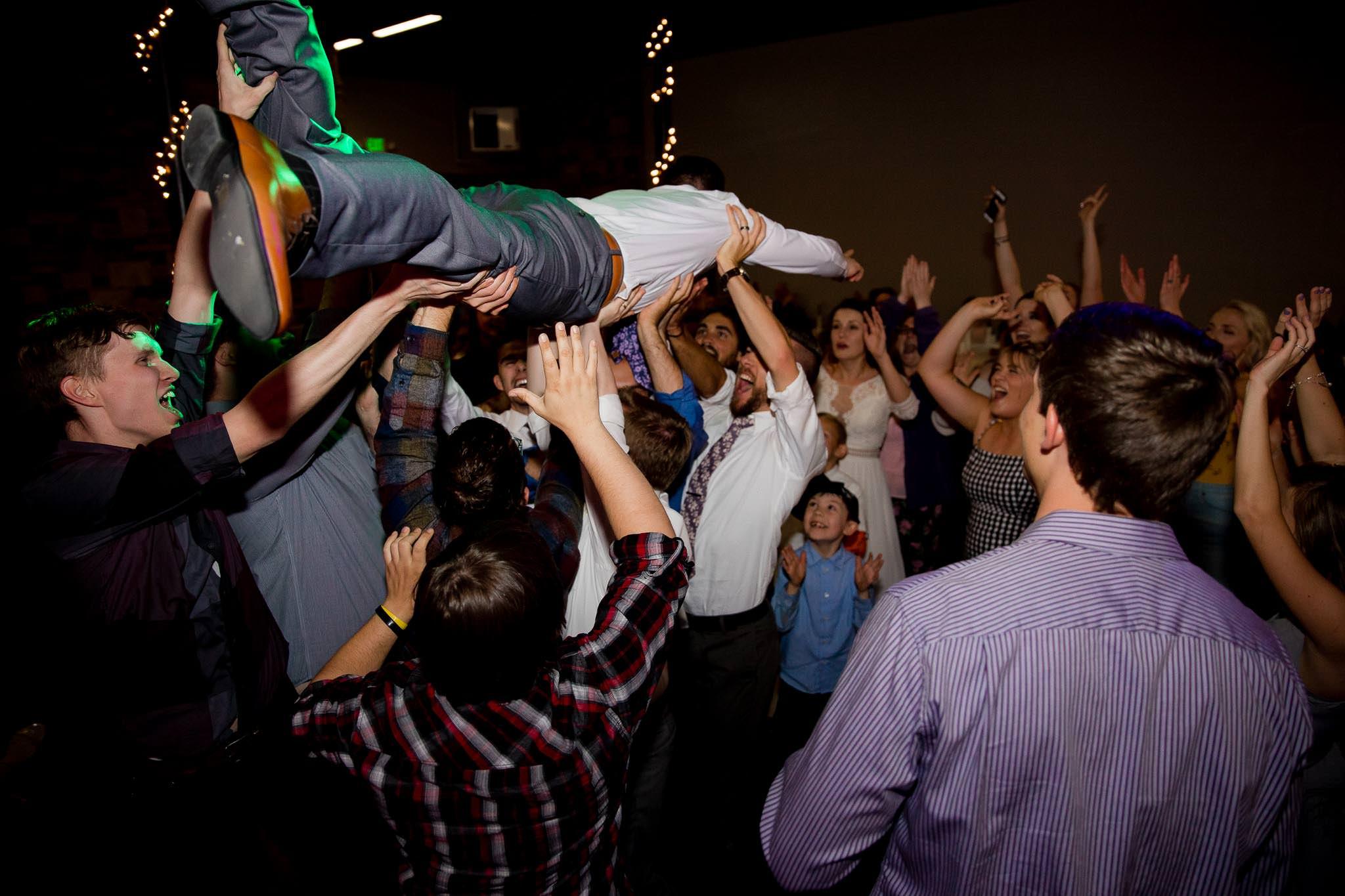 Groom crowdsurfing at wedding reception in Provo, Utah
