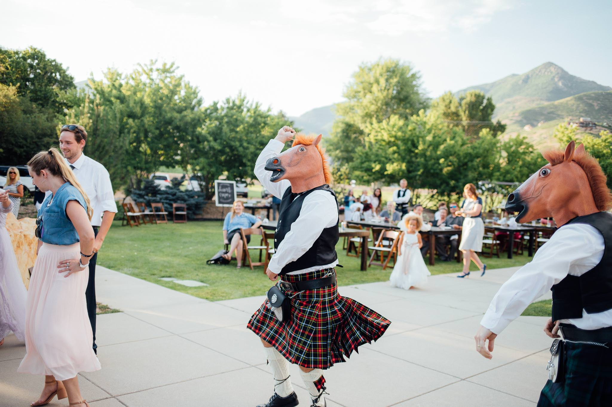 Guest in Scottish kilt and horse head mask dances to Gangnam Style at Midway Utah mountain wedding reception