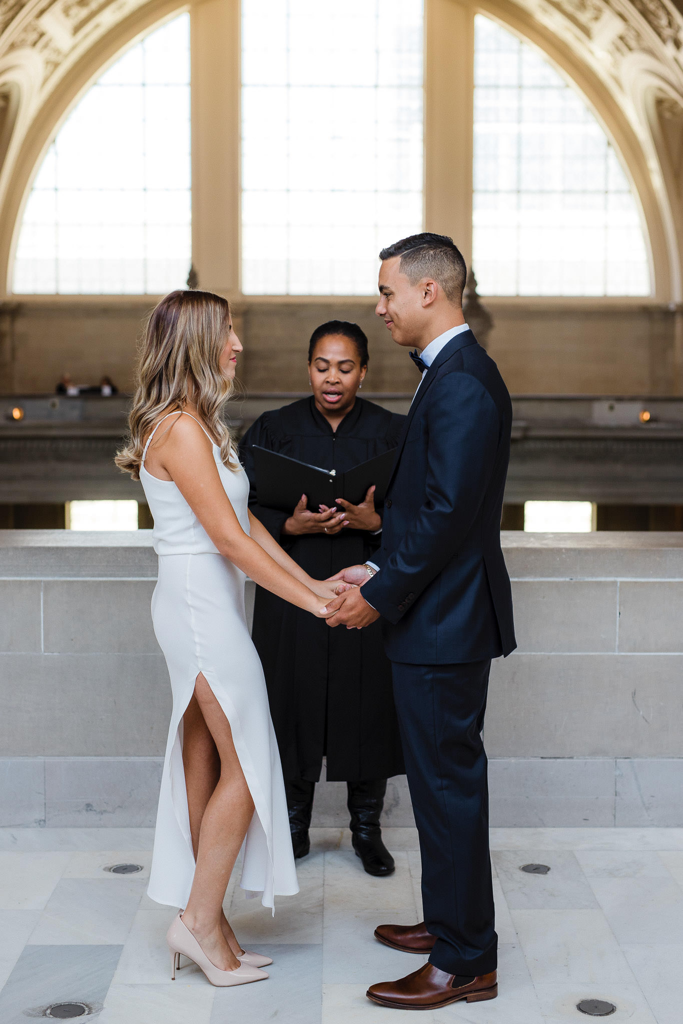 Couple hold hands in front of a justice of the peace during their San Francisco City Hall Elopement