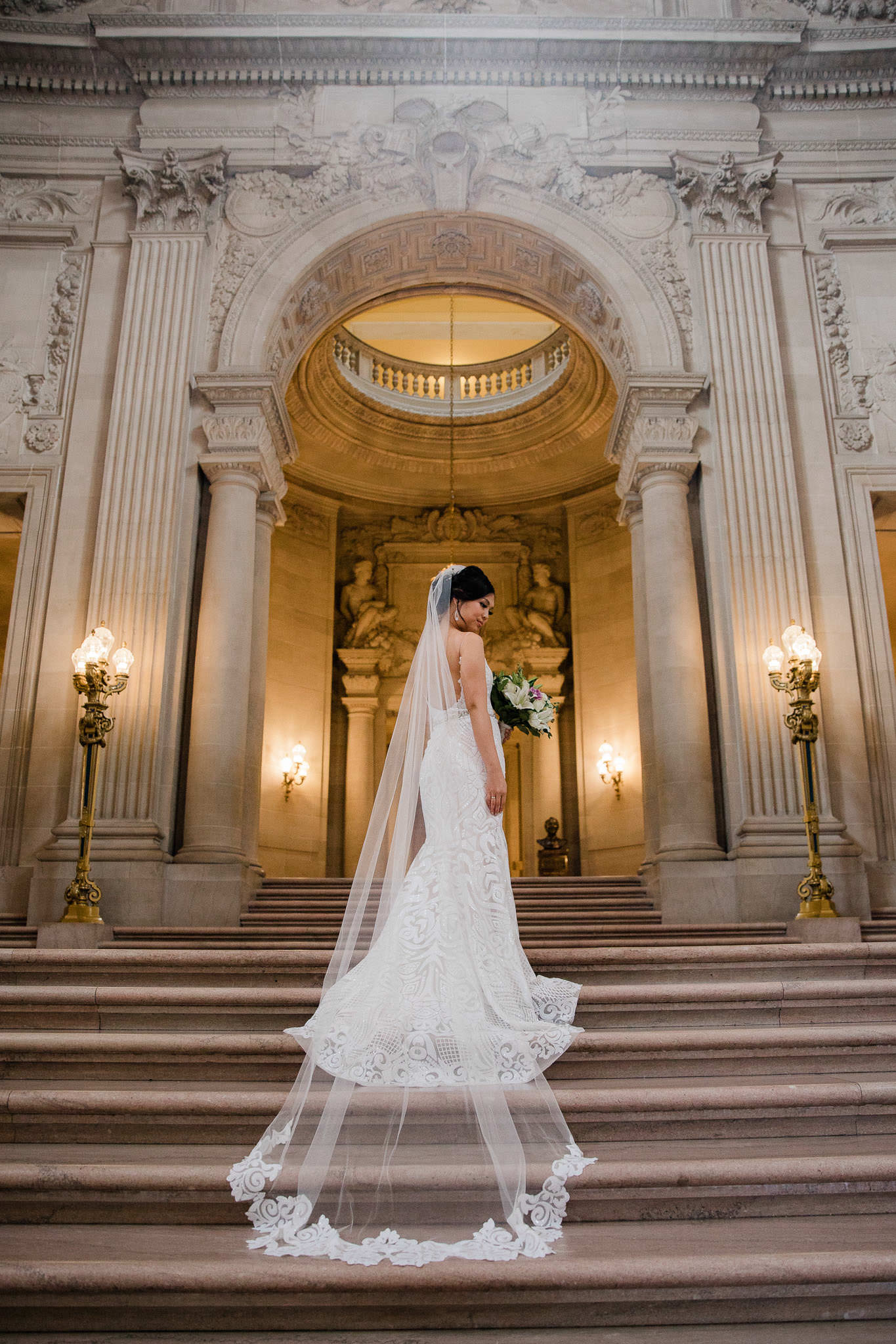 Bride's dress and veil drape down the stairs of San Francisco City Hall