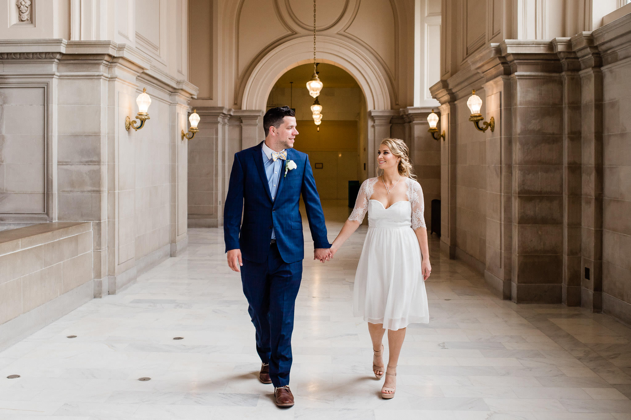 Bride and groom walk in San Francisco City Hall elopement California