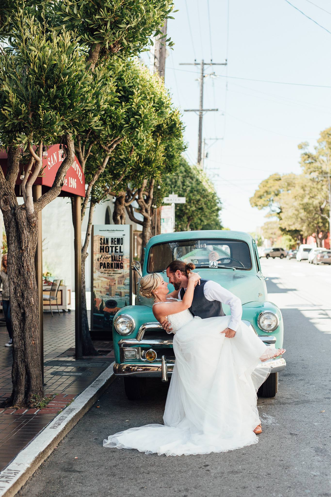 Groom dips bride in front old truck by the San Remo Hotel in San Francisco Elopement