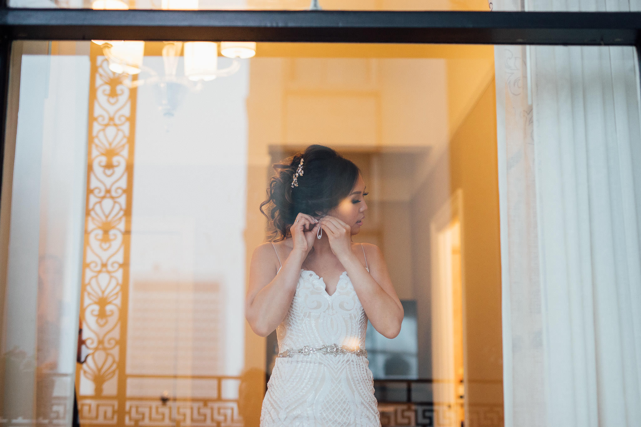 Bride puts earrings on in the San Francisco Fairmont Hotel before her City Hall Elopement