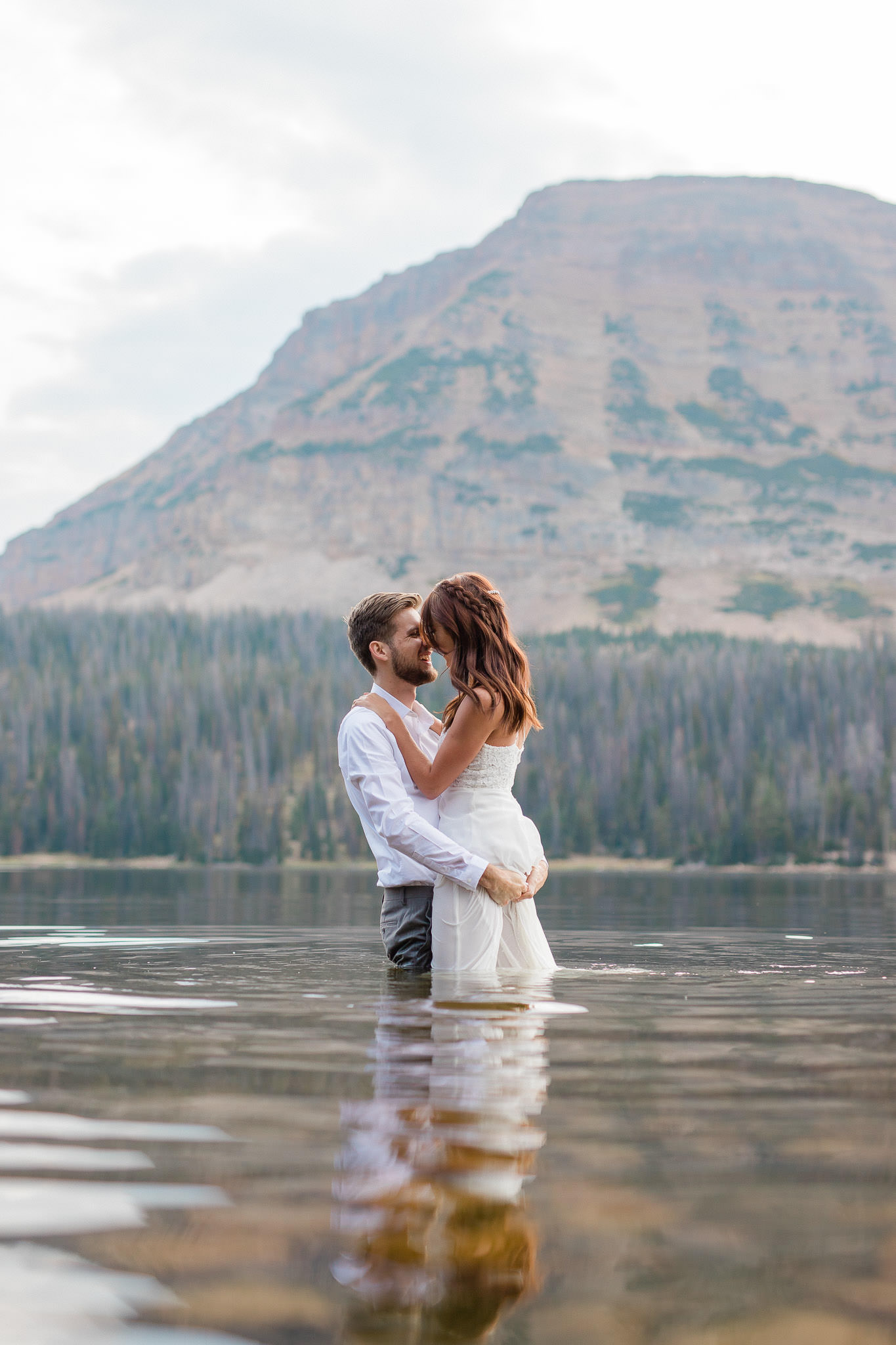 Wedding couple stand in the middle of a lake with a mountain in the background after their elopement ceremony