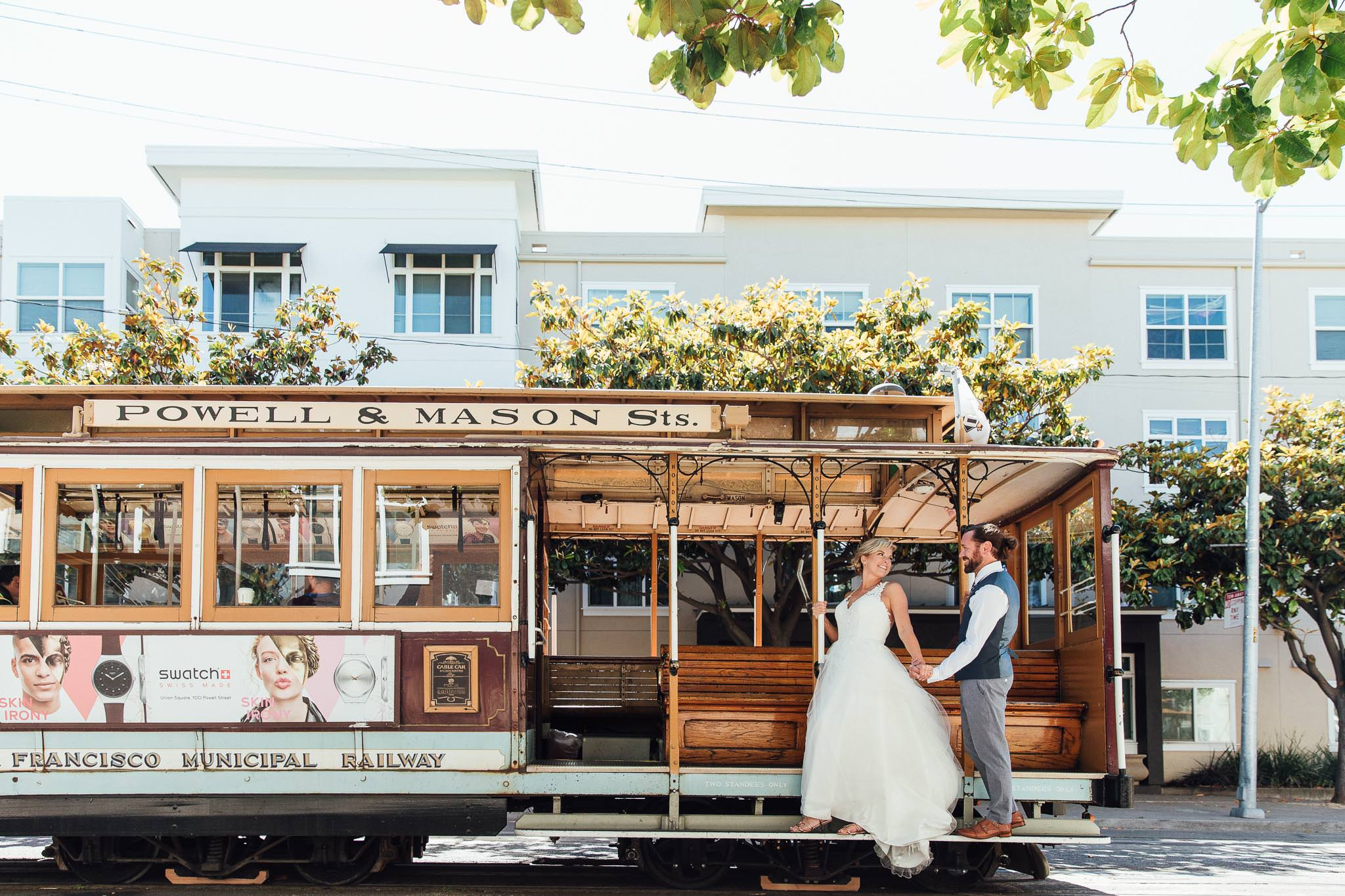 Bride and Groom hold hands and stand on the Powell and Mason Street car in San Francisco