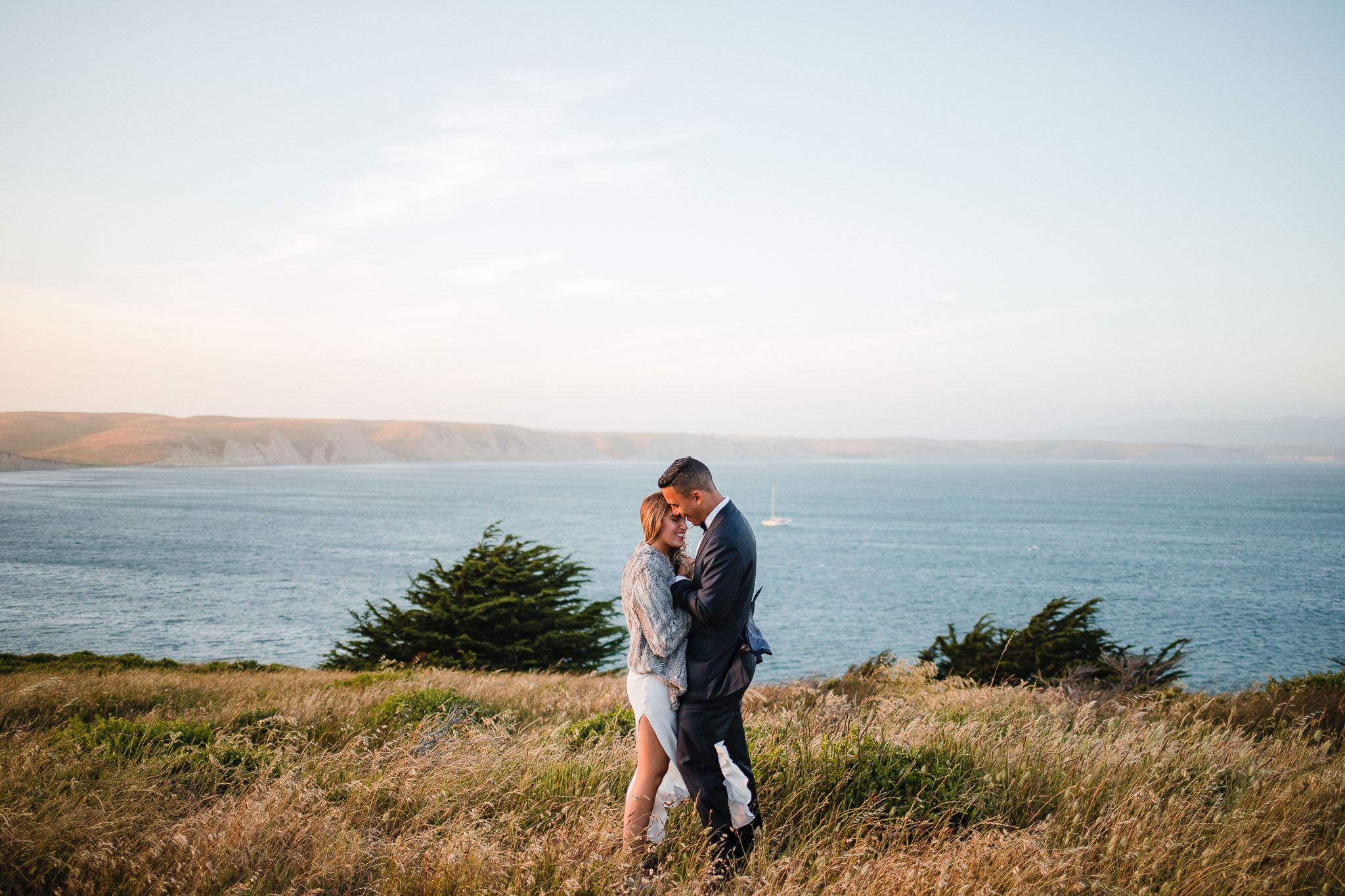 Bride and groom huddle for warmth during sunset at the Point Reyes National Seashore