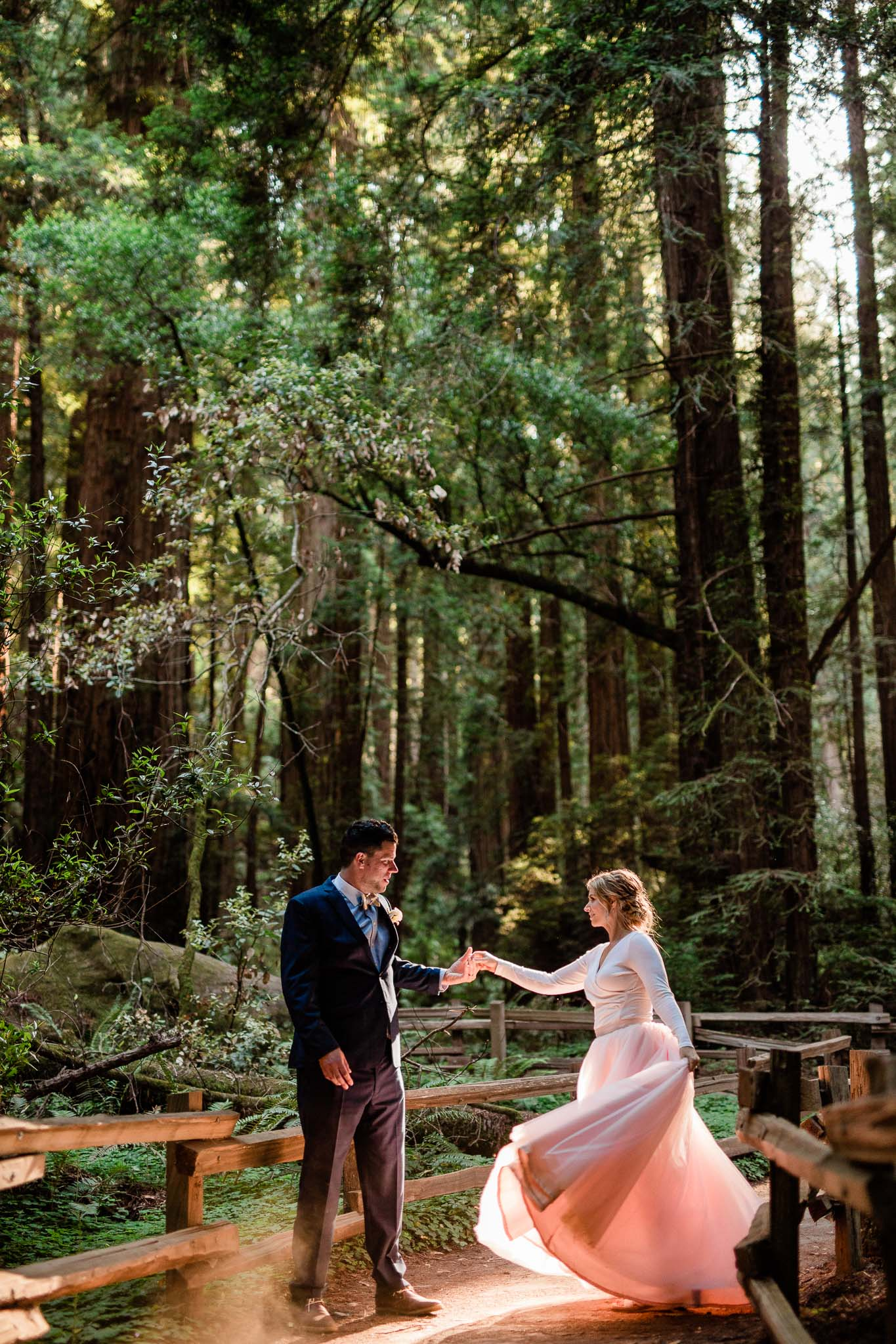 Bride in pink skirt twirls with her groom in a patch of light in the Muir Woods National Monument