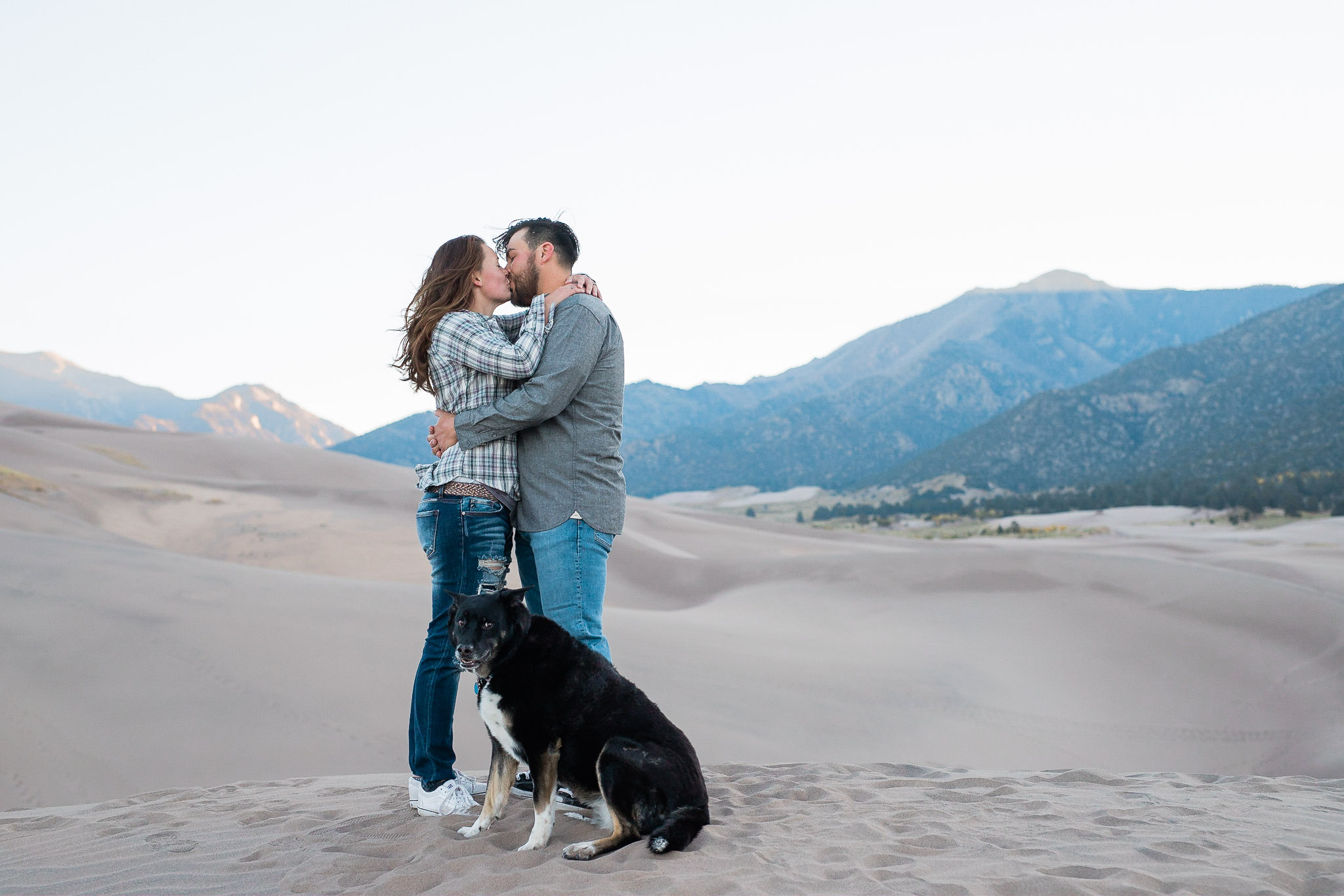 Couple kiss while their dog sits by them for their adventure engagement session at the Great Sand Dunes National Park in Colorado