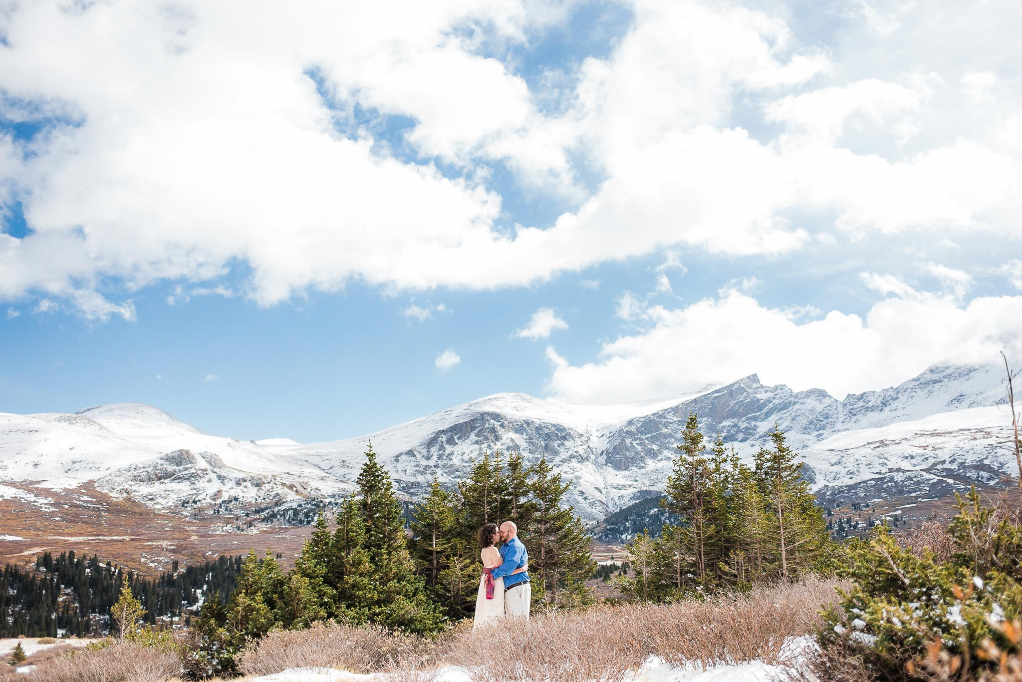 Husband and wife kiss in front of mountain vista including Mt. Beirstadt during their Guanella Pass vow renewal in Colorado