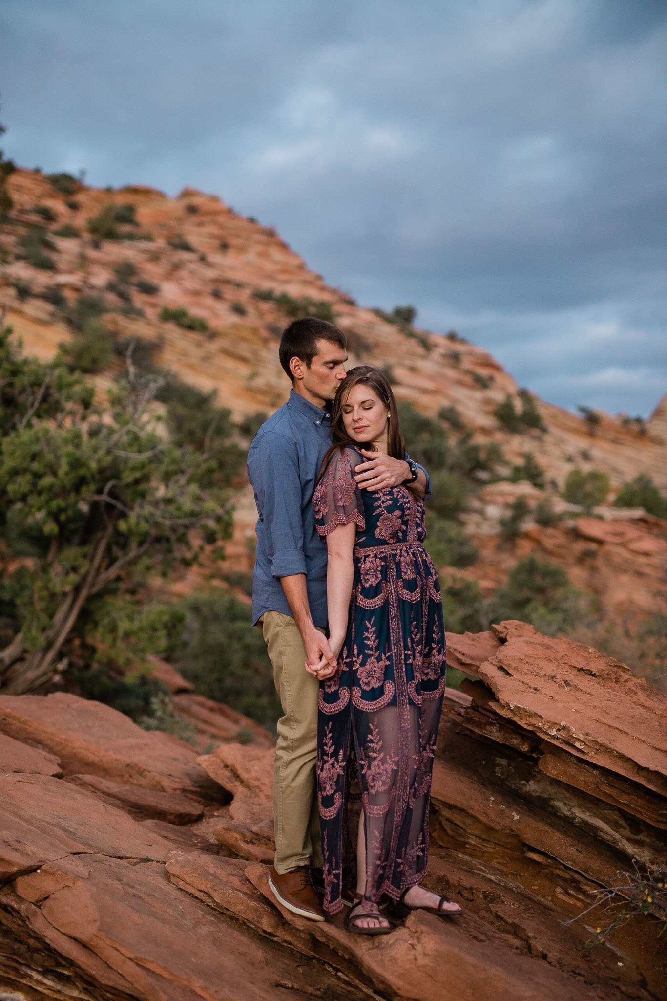 Couple snuggle for intimate portrait during their adventure engagement session in Zion National Park, Utah