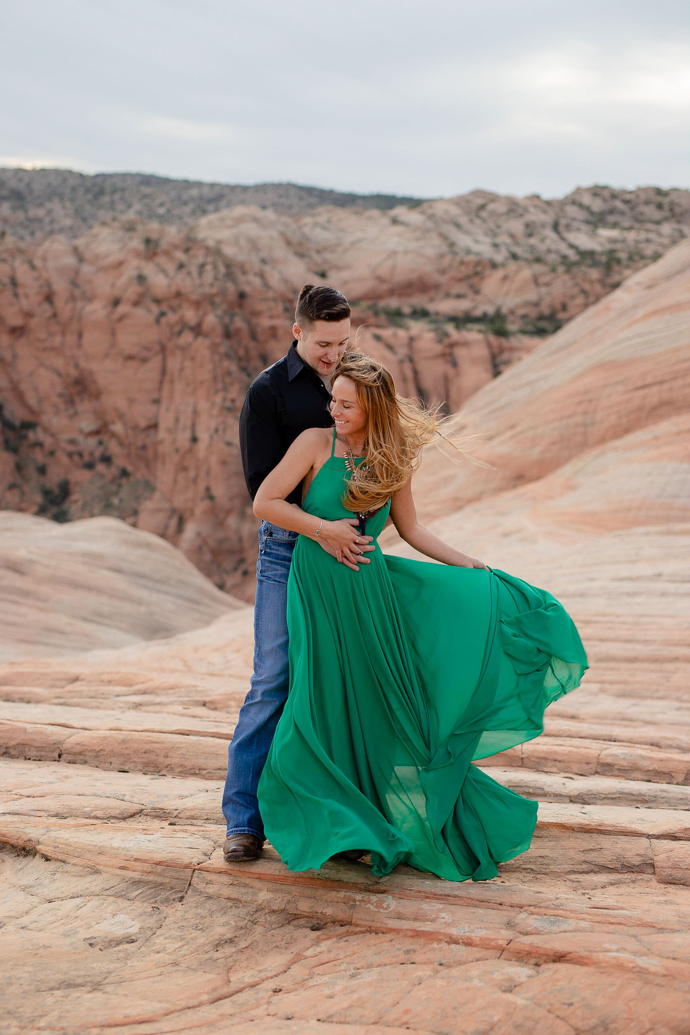 Guy holds girl on a windy day during their Utah adventure session