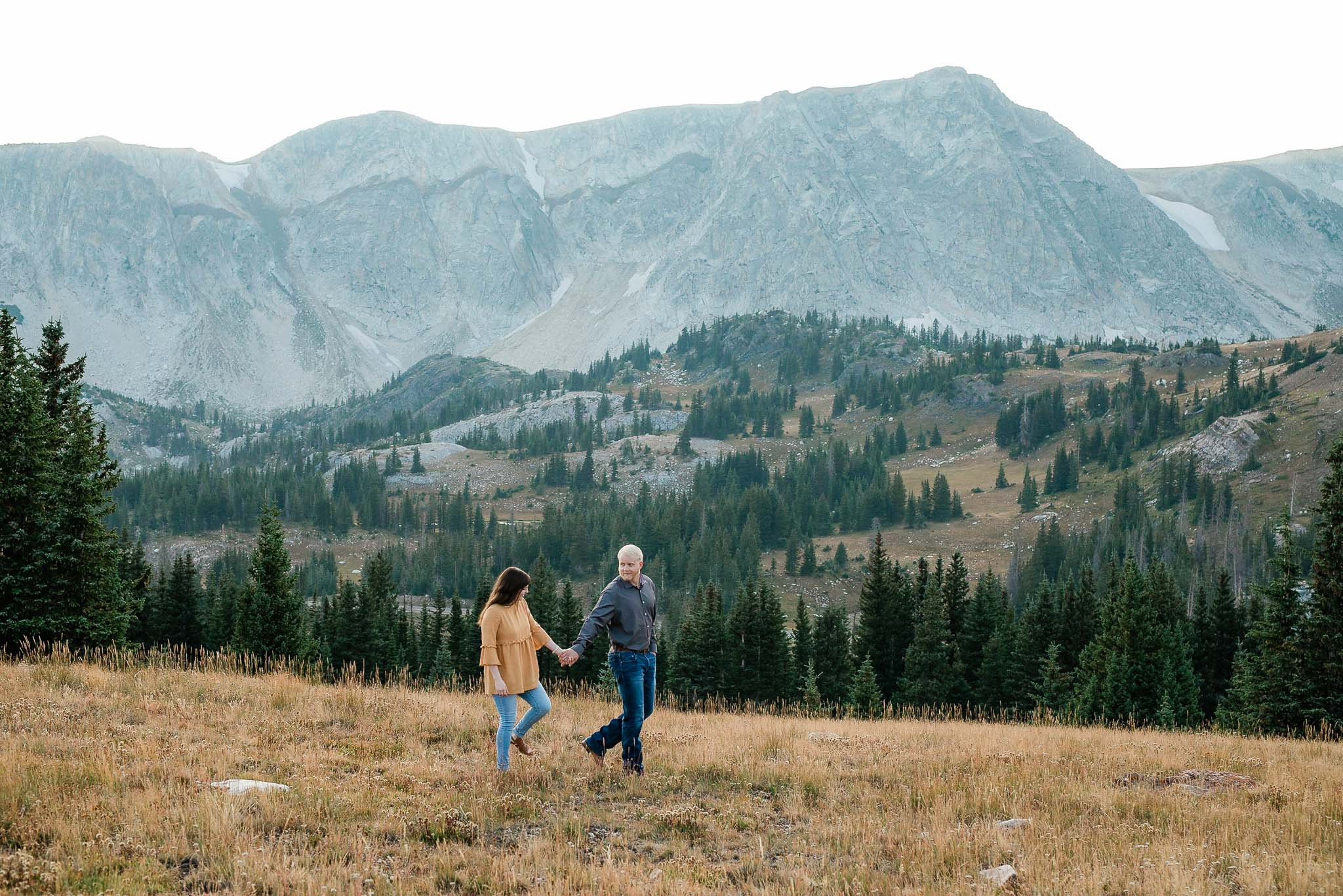 Couple walk together on a field overlooking Medicine Bow Peak for their Wyoming adventure session