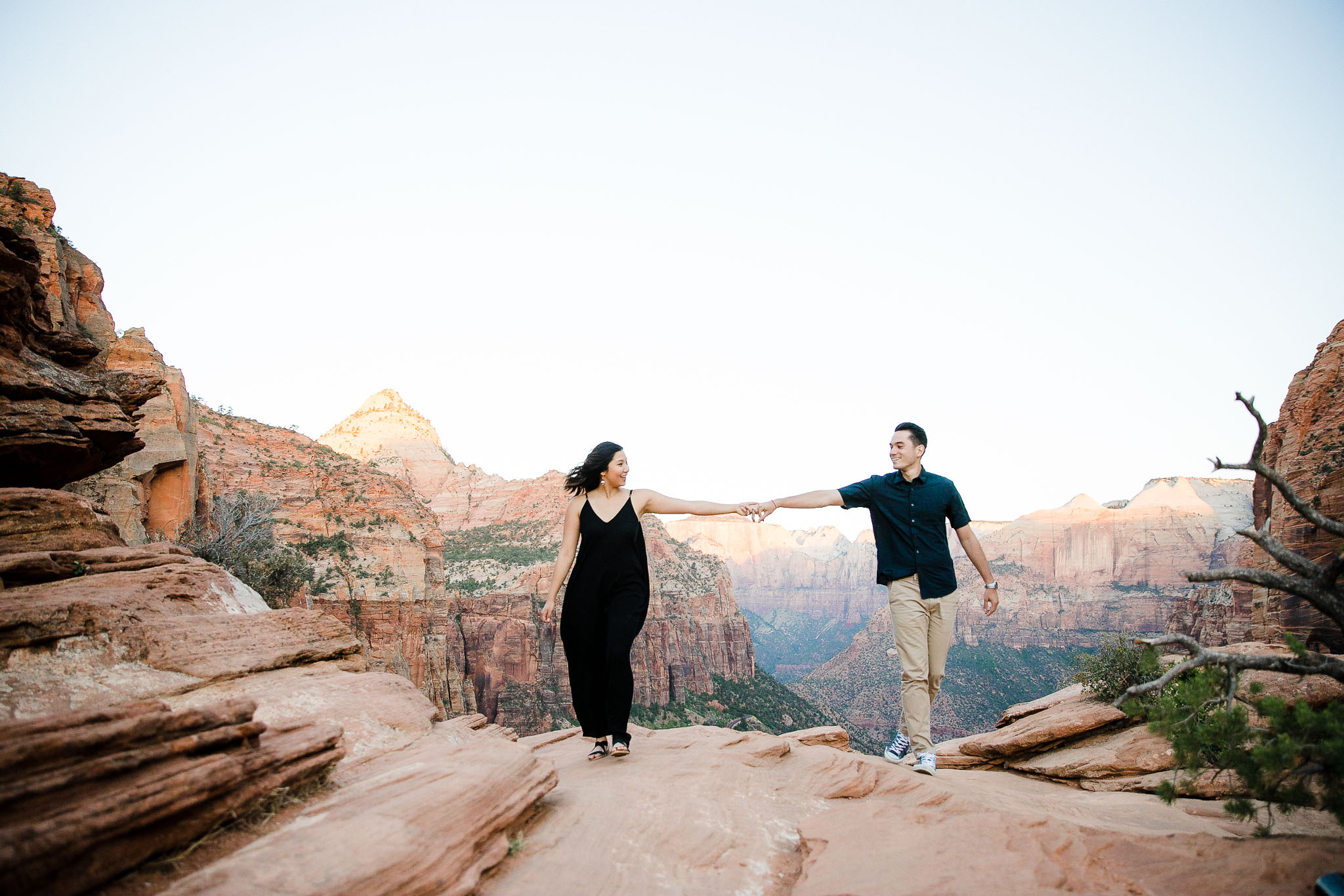 Couple walk and laugh together at Canyon Overlook in Zion National Park during their adventure session