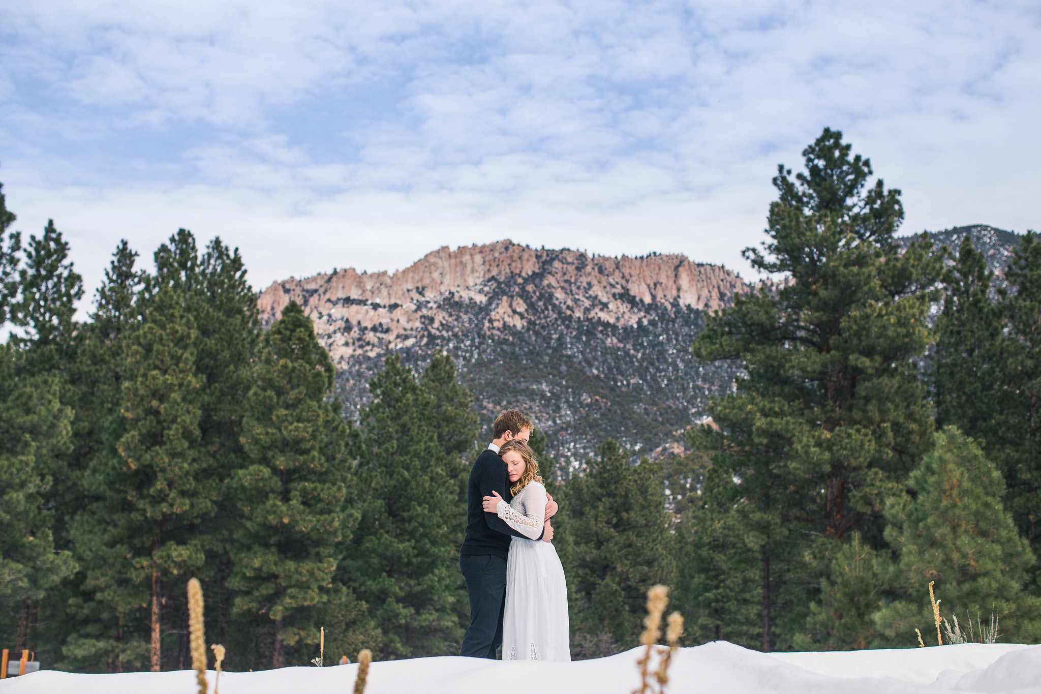 Bride and groom embrace in the snow during their Utah adventure wedding