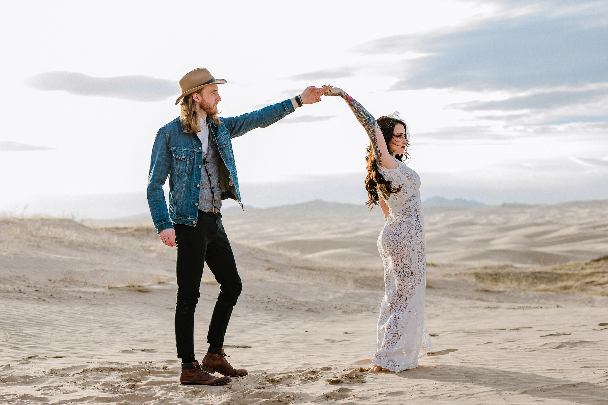 Alternative wedding couple dance during their adventure session at the Little Sahara Sand Dunes in Utah
