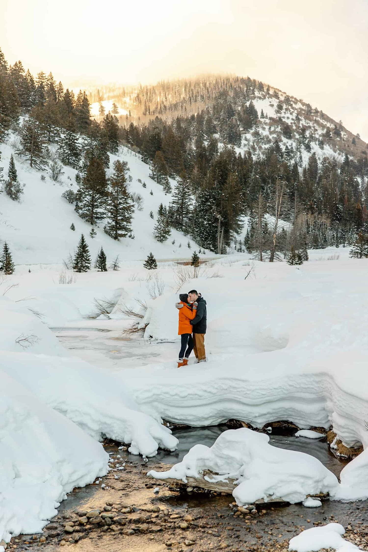 Couple kisses during their snowy Utah outdoor engagement session in the winter, Big Cottonwood Canyon
