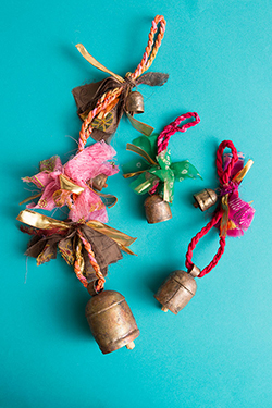 ENCHANTING ORIGINS OF BELL MAKING - Bells! Twisted saris for string. Sparkly ribbons for accents. Iron with copper coating hand shaped for resonance.How are these bells made?